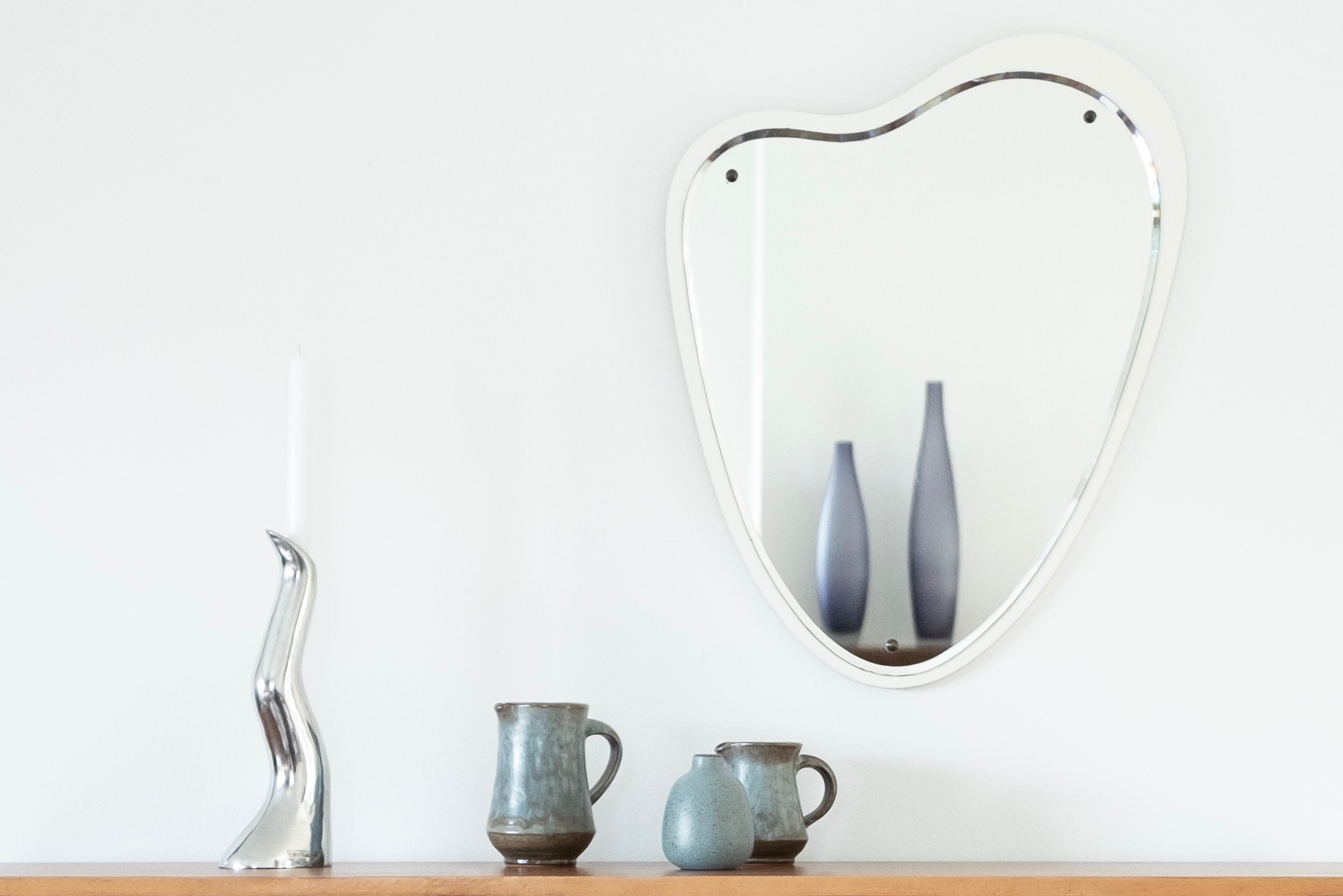 Close up image of silver Anna Efverlund design candle holder and small vases on sideboard with vintage mirror