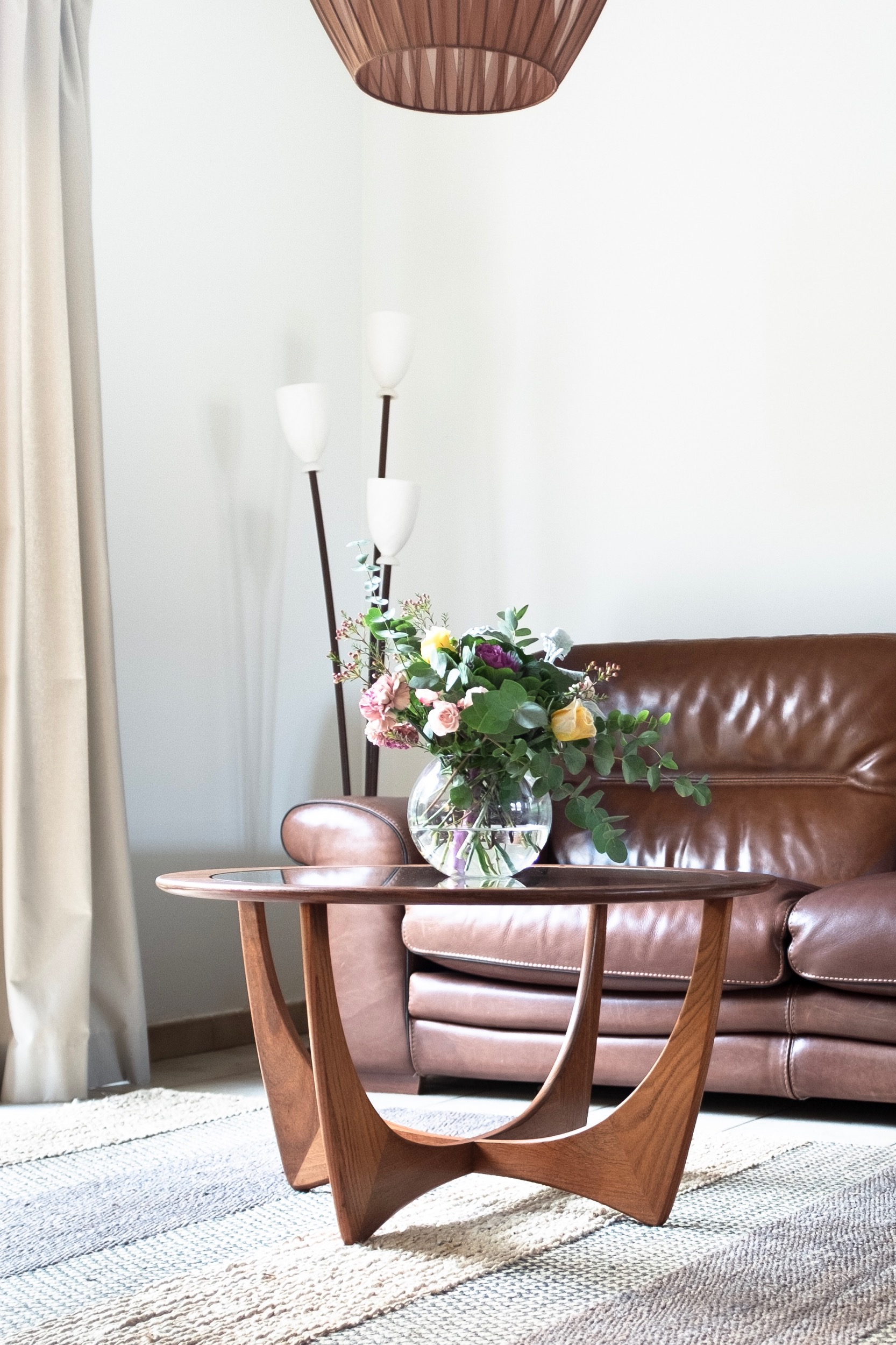 Round vintage wood coffee table with flowers in front of leather couch and tulip lamp