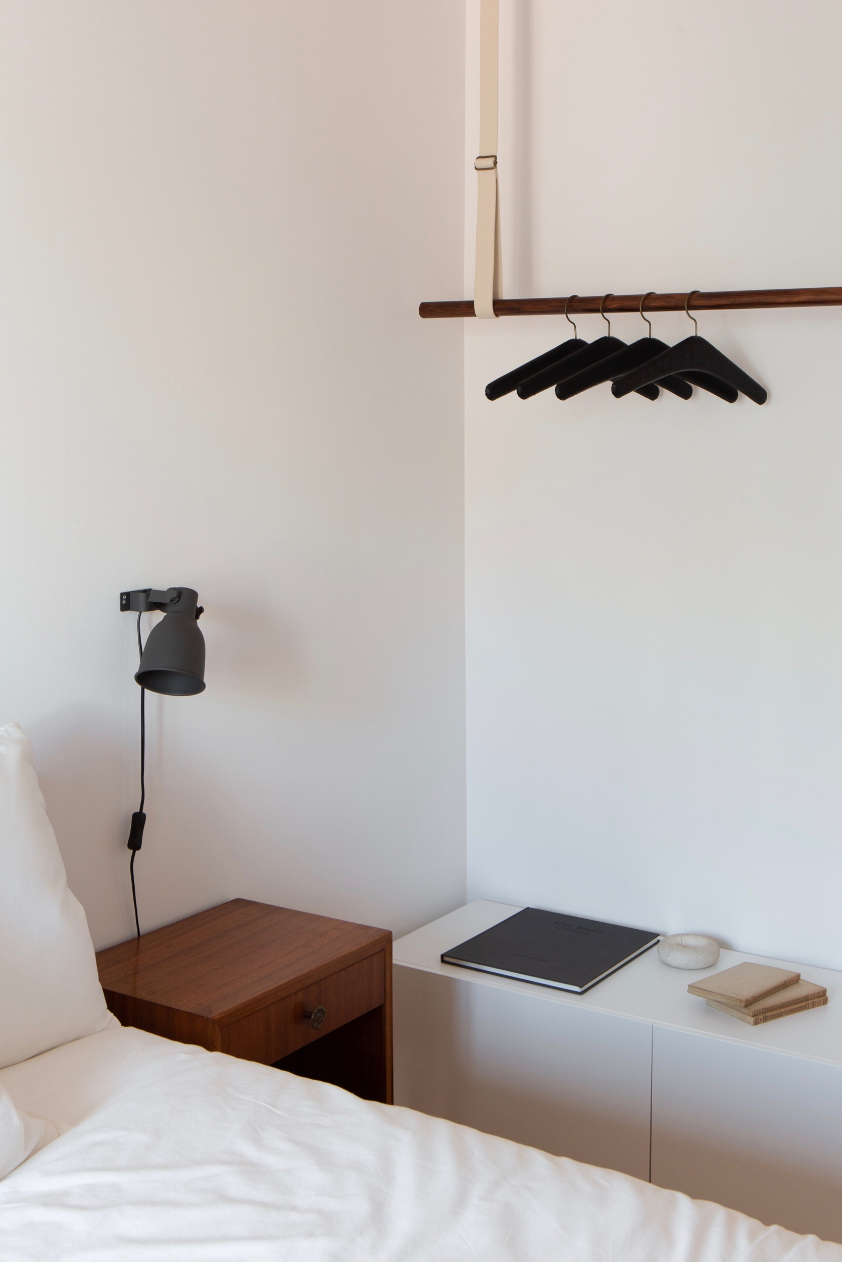 Detail photo of Lola Cwikowski Studio Travessa da Pereira Apartment residential project showing bedroom with vintage nightstands and custom clothes hanging system with vintage black leather hangers.