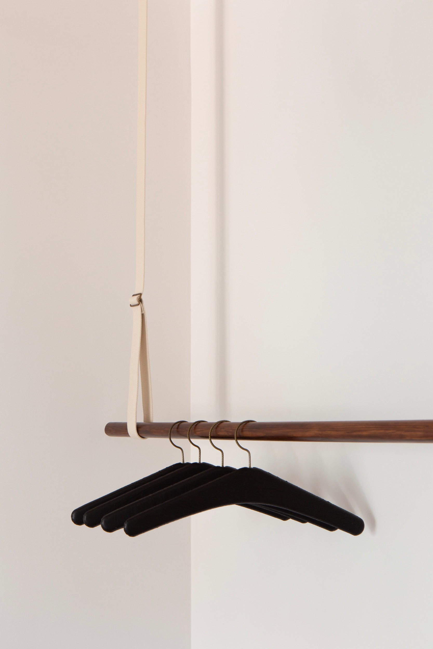 Detail photo of Lola Cwikowski Studio Travessa da Pereira Apartment residential project showing bedroom custom hanging system with vintage black leather hangers.