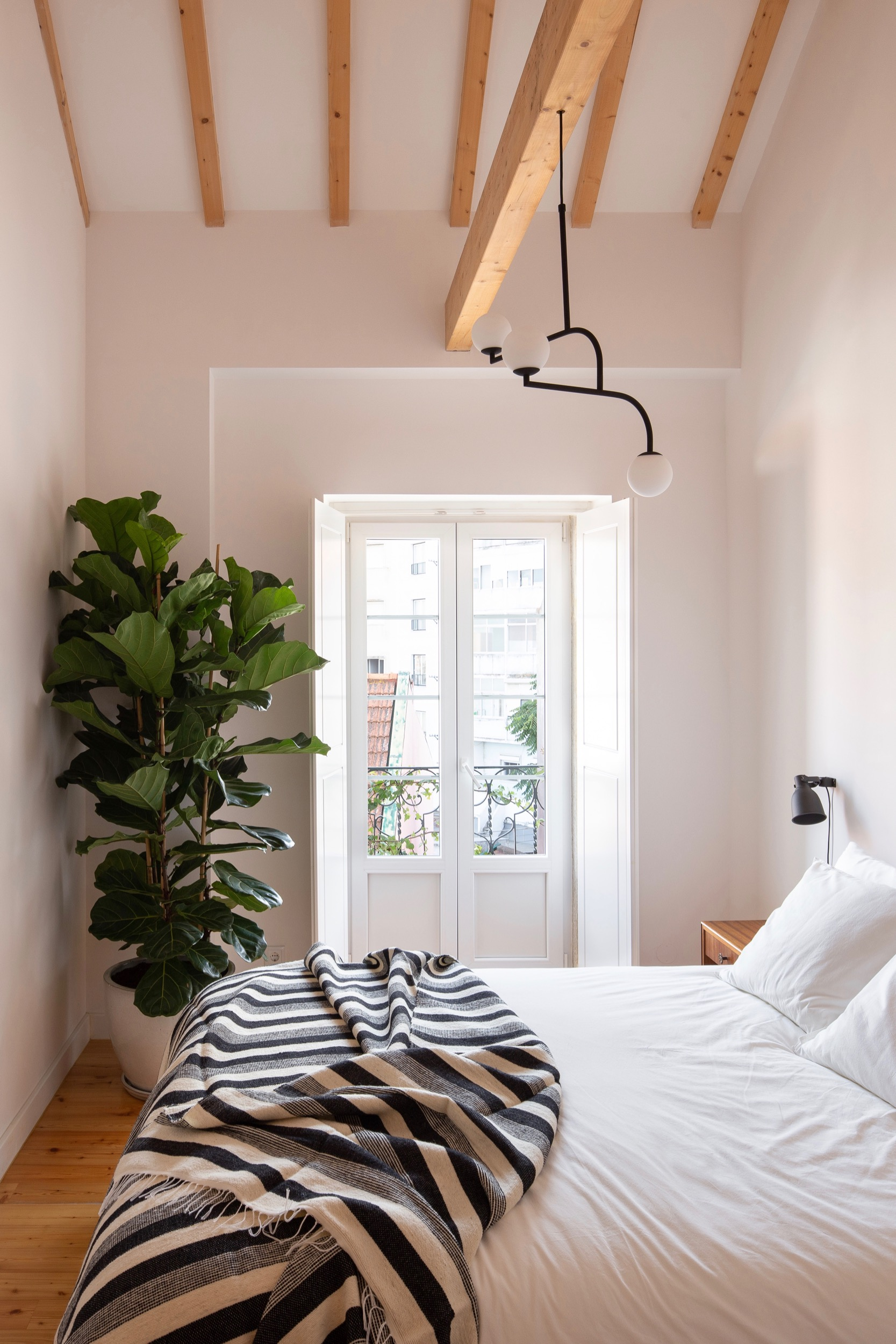 Photo of Lola Cwikowski Studio Travessa da Pereira Apartment residential project showing bedroom with Portuguese wool blanket, vintage nightstands, customized bed frame, and large ficus plant.