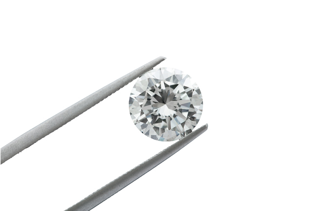 loose brilliant round diamonds is being held by tweezers on blac