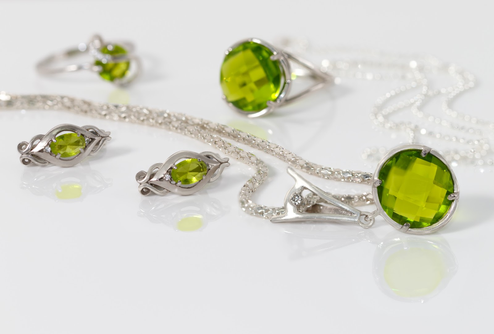 Close-up beauty silver pendant, earrings with peridot on background  chain and rings on white acrylic desk.