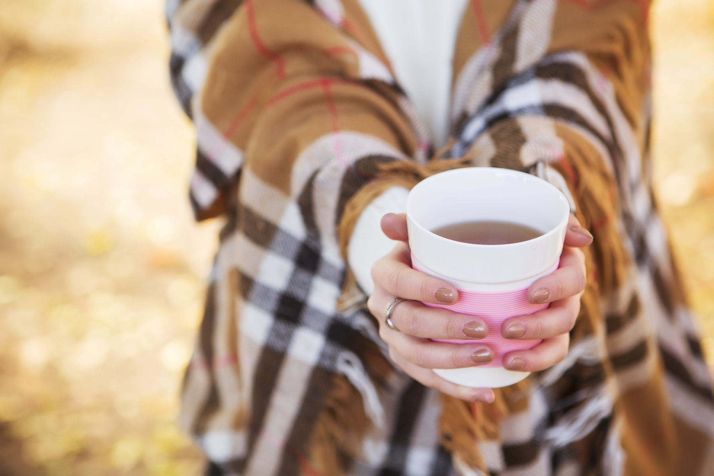 Beautiful caucasian brunette young woman in warm autumn day at park. Yellow leaves and sunshine. Fall season. Woman in white sweater and plaid with a cup of coffee in hands, smiling. Copy space