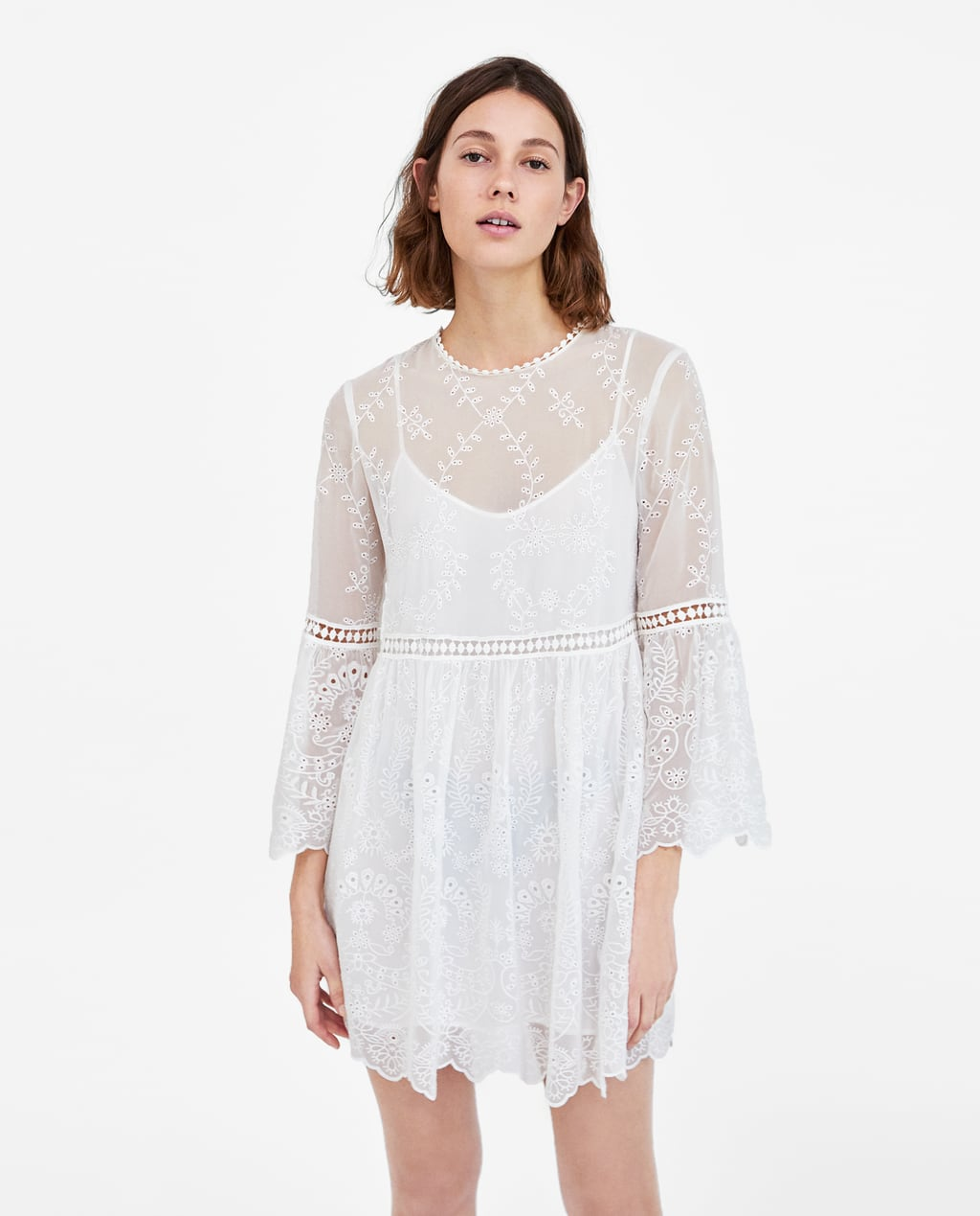 - Semi-sheer dress with a round neckline and long sleeves with ruffles from the elbow down. Features matching hemstitched appliqués, a cinched waist, an A-line silhouette with gathered details, matching lining and a buttoned opening in the back.