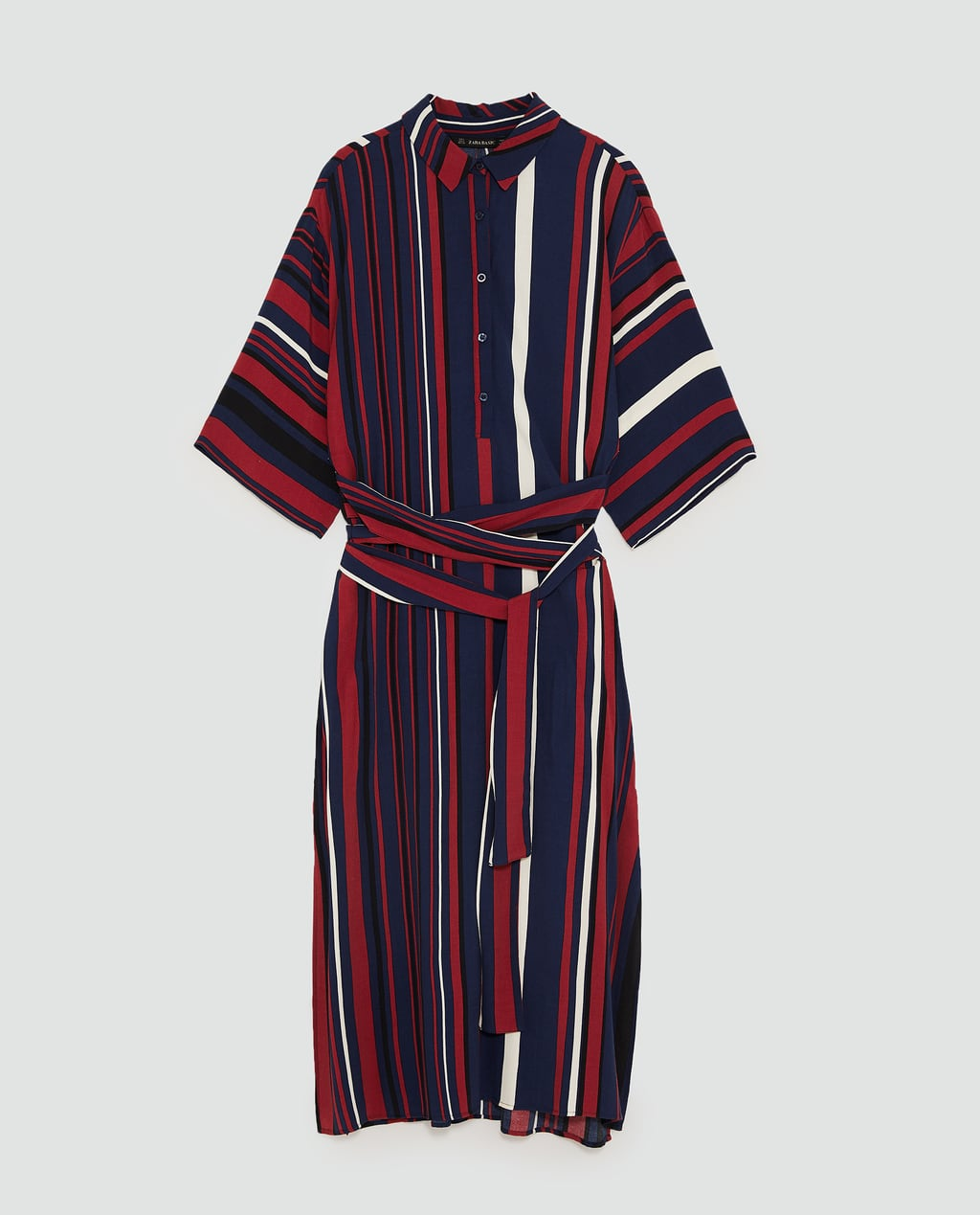 - Tunic with lapel collar and sleeves that reach below the elbow. Features a crossed fabric belt detail in the front, side slits at the hem and button fastening in the front.