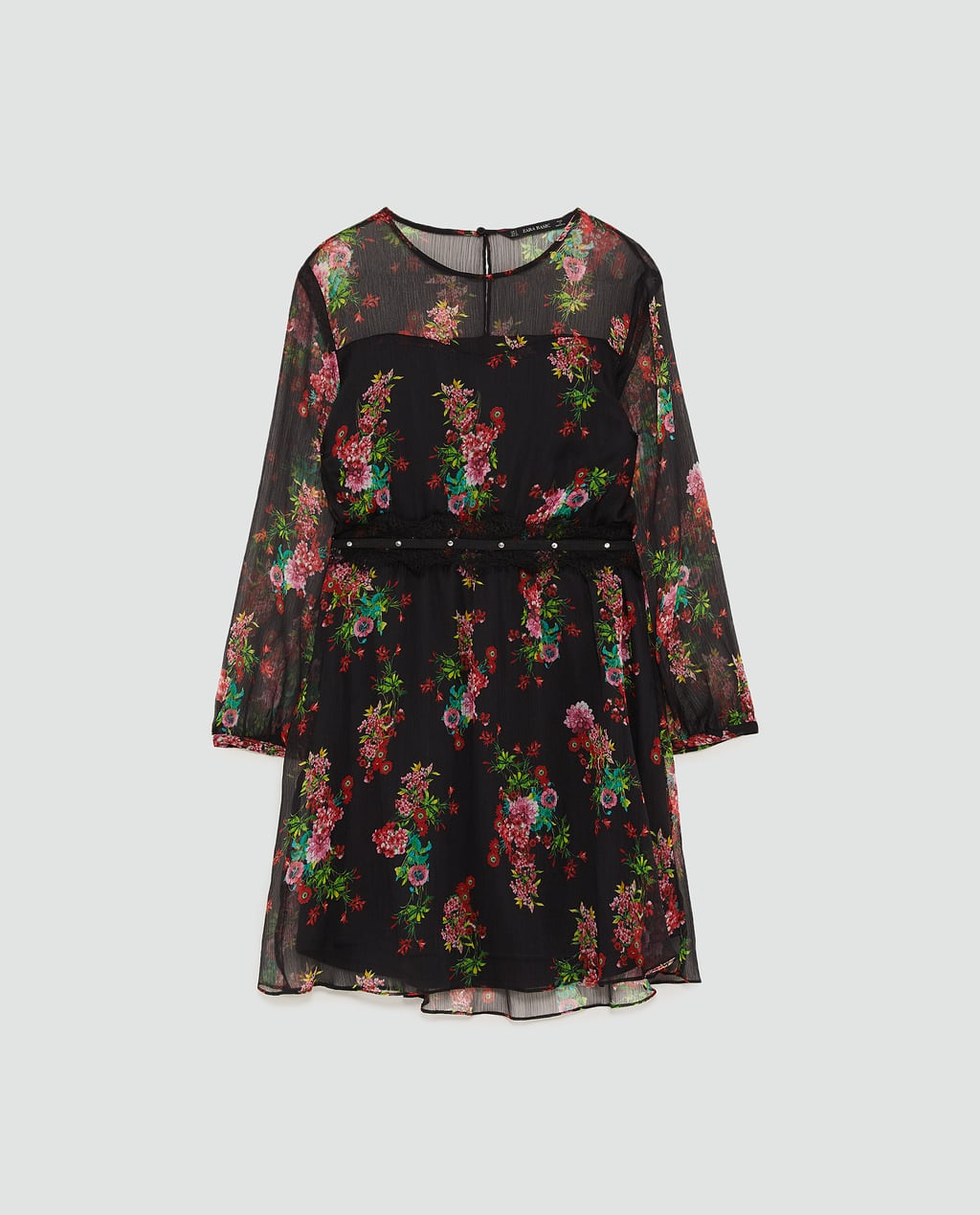 - Flowing round neck dress with long sleeves and elastic waist. Features a lace appliqué detail with studs, matching interior lining and a buttoned opening in the back.