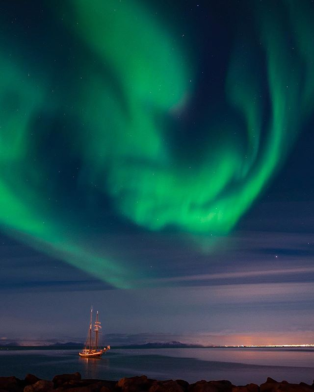 A giant green alien hovers over Reykjavík harbor as unknowing passengers on a sailboat sleep. . . #iceland #auroraborealis #sailboat #landscapephotography #nightsky #greengoddess #travelphotography #green #babakworkshops