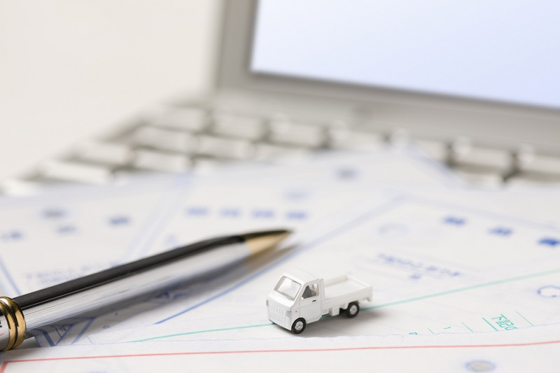 A pen and a car model on a laptop