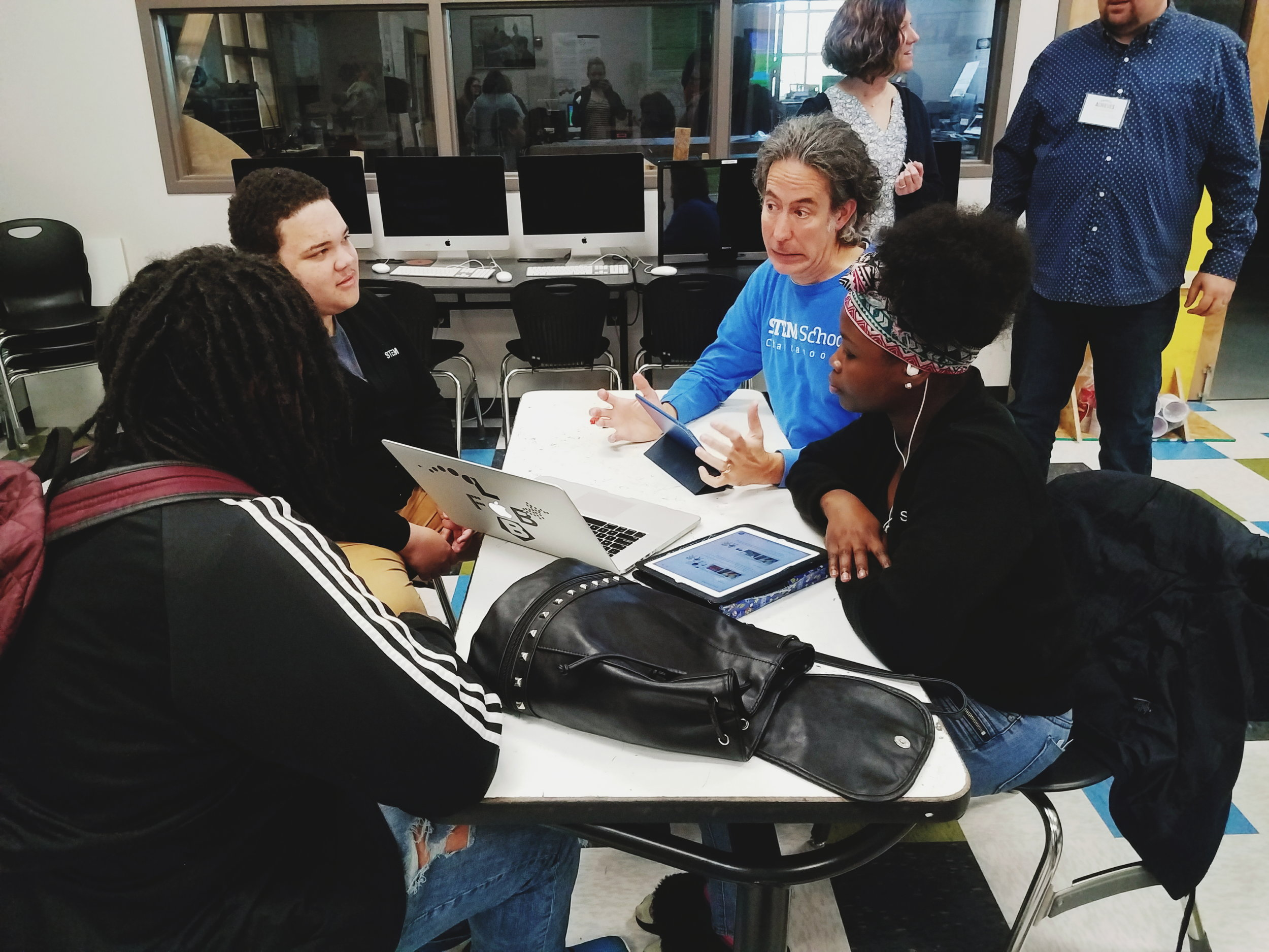 A teacher at STEM School Chattanooga offers insights and support to students on their group project.