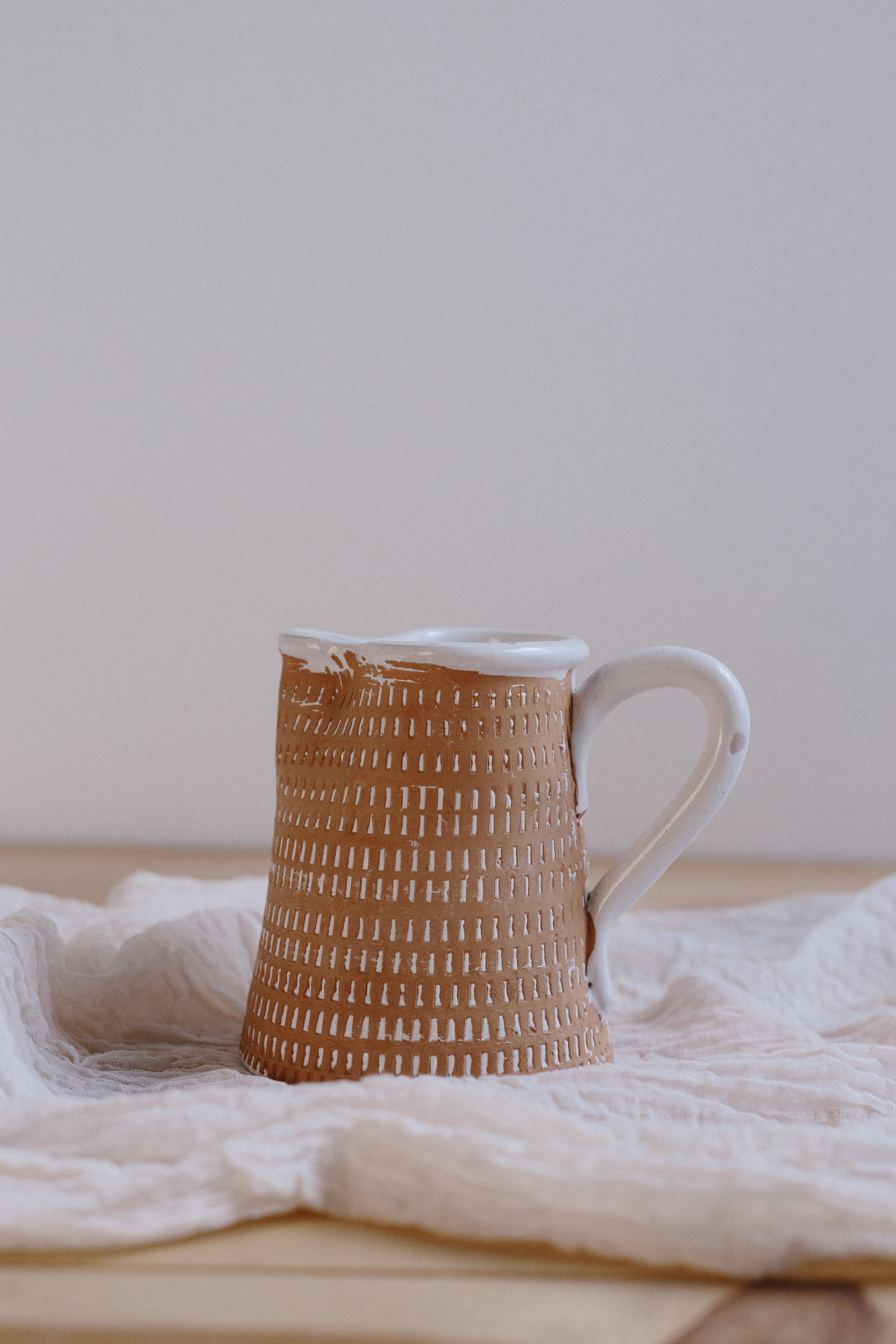 WHITE AND TAN CERAMIC PITCHER // $6