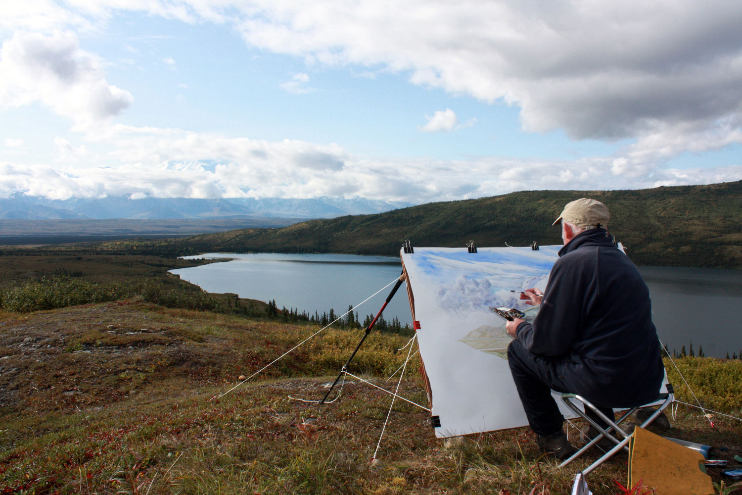 Tony Foster painting in Denali National Park, Alaska, August, 2014. Photo by Becky Williamson. Courtesy Foster Art & Wilderness Foundation.  (Painting is  Denali and Wonder Lake Looking South from Ansel Adams Point , 2014. Inventory #2007.1.6)
