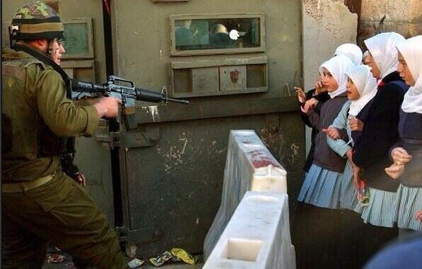 At a checkpoint in Hebron, police point guns at children as the make their way to school.