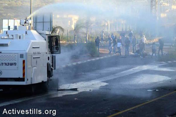 Israeli National Police use water cannons to douse protesters with putrid skunk spray.