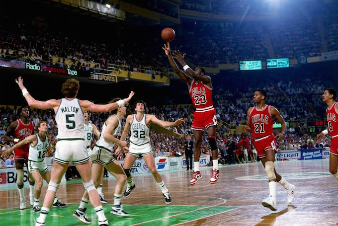 (Caption: Michael Jordan takes a jump shot against the Celtics on his way to a playoff-record 63 points. Jordan is clad in the soon-to-be famous red and black of the Chicago Bulls, while the Celtics wear their classic white and emerald kits. Both teams are examples of the practical, minimal tone for uniform design set over the first several decades of the NBA). Source: https://sneakerbardetroit.com/michael-jordan-63-points-boston-celtics/