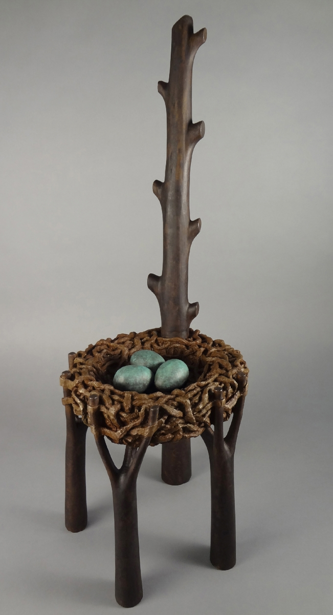 """BirdNest Chair - There are two stories here. The first is the origin of this piece, which was carved from a pine tree in our yard that blew over in a storm. The previous year, it had a Crow's nest at the very top from which I watched a (big) baby take its first flight....which was not very graceful as it bounced from one padded limb to another, buffering its fall to the ground. All was well as the parents called to the baby from the woods and Baby Crow followed the voices and the family was reunited.Size:33.25"""" x 12"""" x 12.5""""Medium:Bronze (The first casting of ten castings has been sold. You are not too late...there are nine more!)Price:$6,400Purchase through Harbor Square Gallery"""