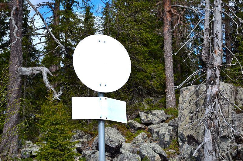 Tervetuloa Syötteen kansallispuistoon. Nämä rajakyltit ovat yleensä sinisiä, mutta tuuli lienee repinyt maalin irti.