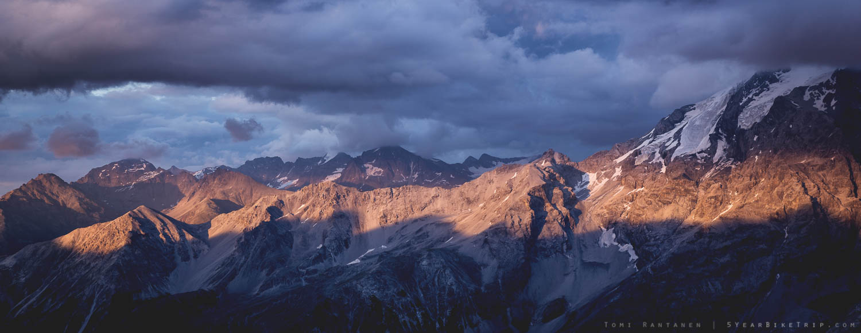 Auringonvalo piirtää muotojaan vuorien ja pilvien välistä.