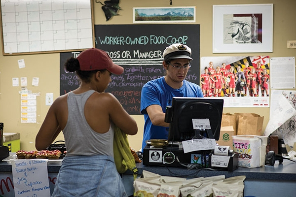 Xavier Moncayo-Escala, a fifth year economics major, rings up a customer at the cash register of the Maryland Food Collective in The Stamp Student Union. The Co-op is celebrating its 40th anniversary.