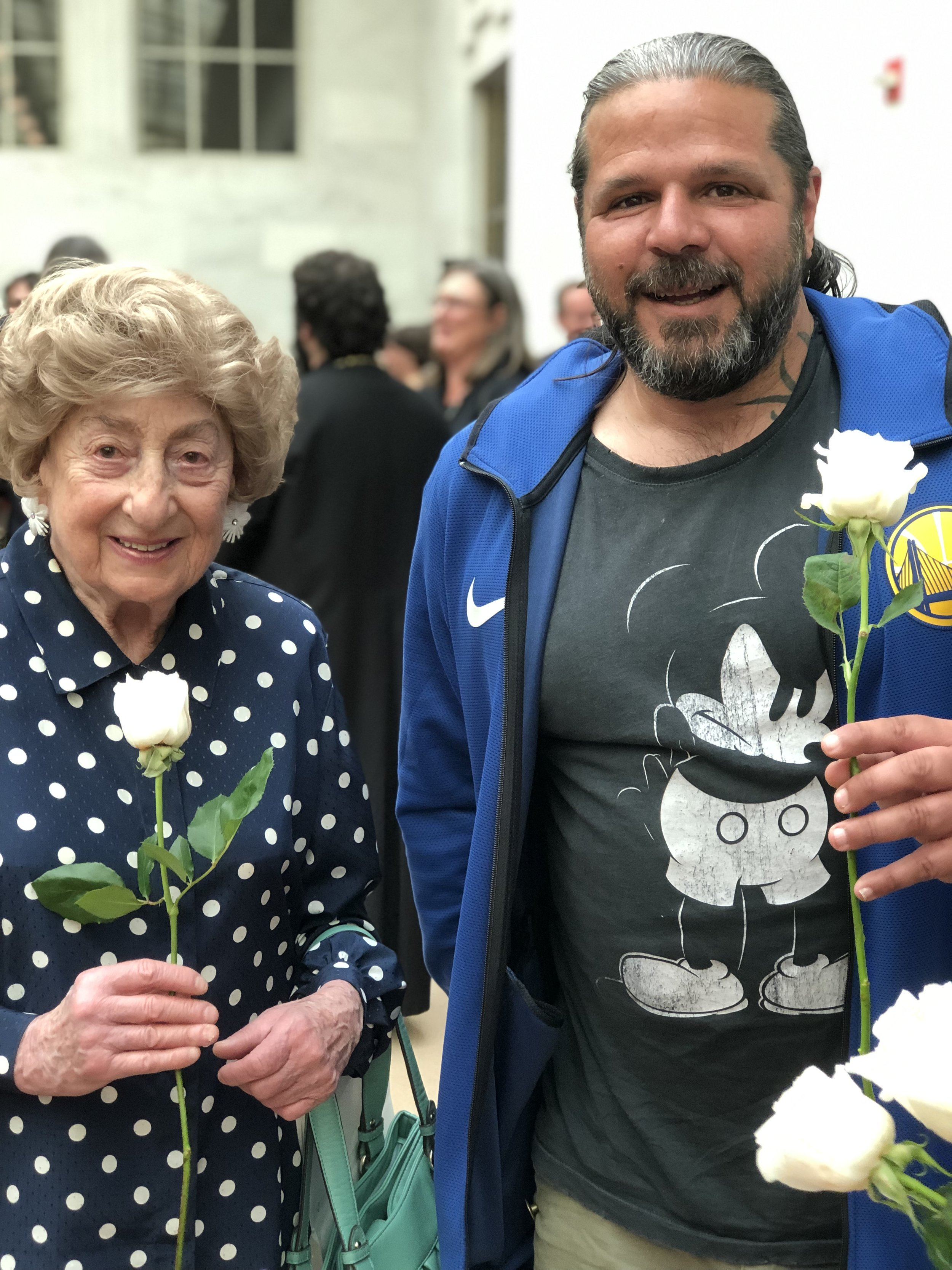 A Holocaust Survivor with the artist, Luigi Toscano, holding a symbolic flower of freedom to represent The White Rose Movement, led by Sophie Scholl, founder of the peaceful resistance movement against the Nazi regime.