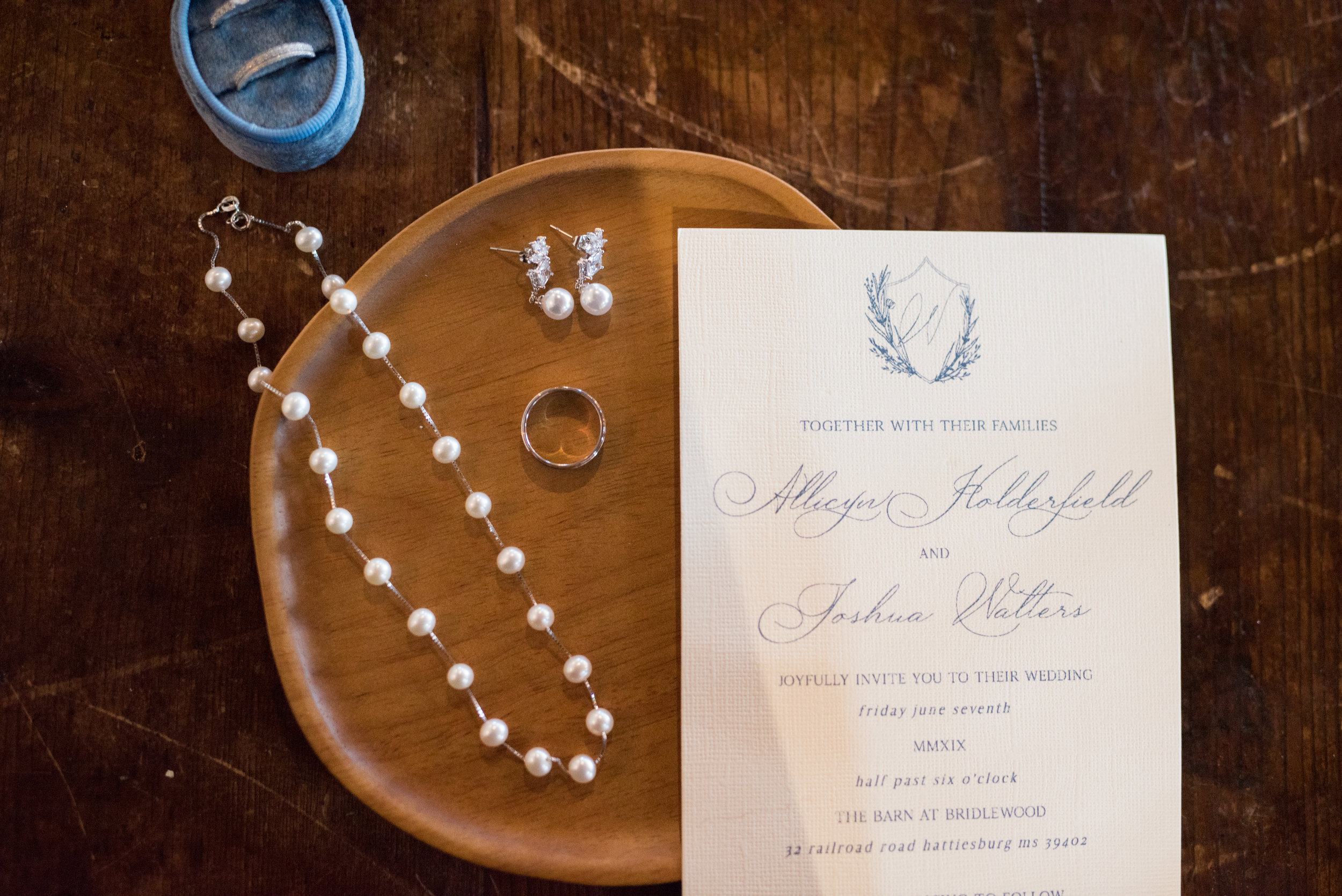 The Barn at Bridlewood wedding in Hattiesburg, Mississippi (MS) in June | Bride's wedding rings in a Mrs. Box, earrings, stationary, groom's ring, pearls, necklace, and details