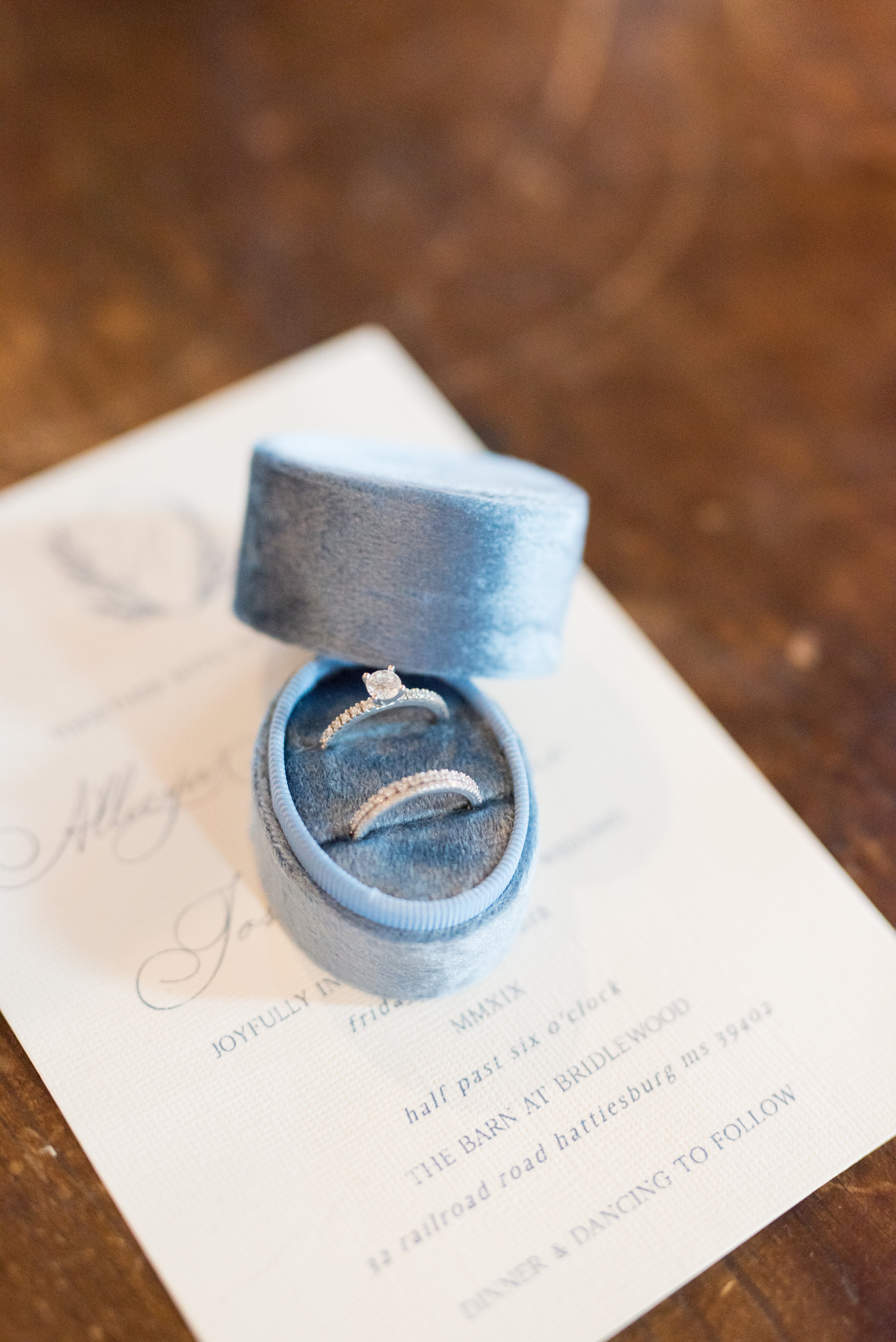 The Barn at Bridlewood wedding in Hattiesburg, Mississippi (MS) in June | Bride's wedding rings in a Mrs. Box, stationary and, details