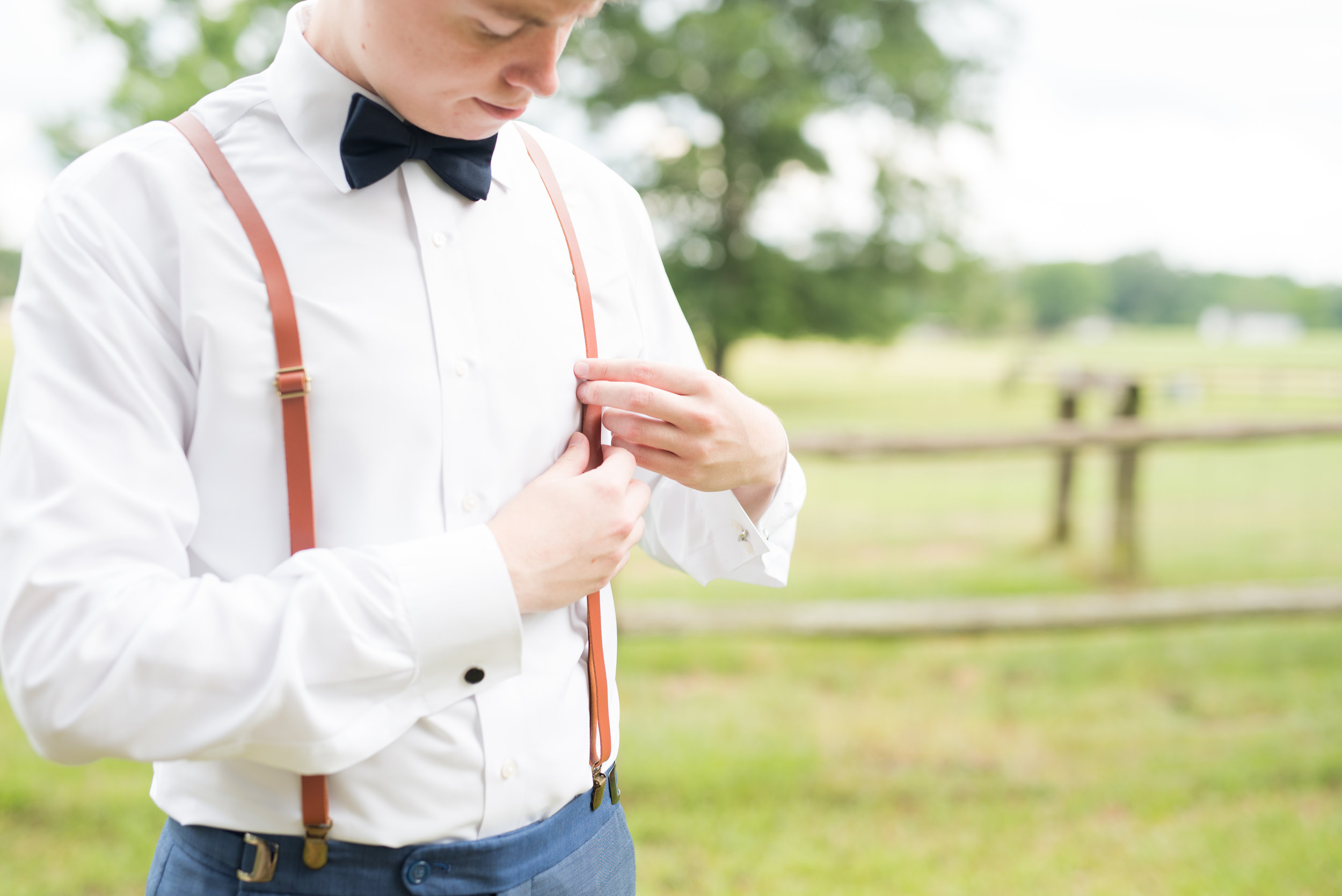 The Barn at Bridlewood wedding in Hattiesburg, Mississippi (MS) in June | the Groom getting ready for the wedding wearing suspenders and a bowtie
