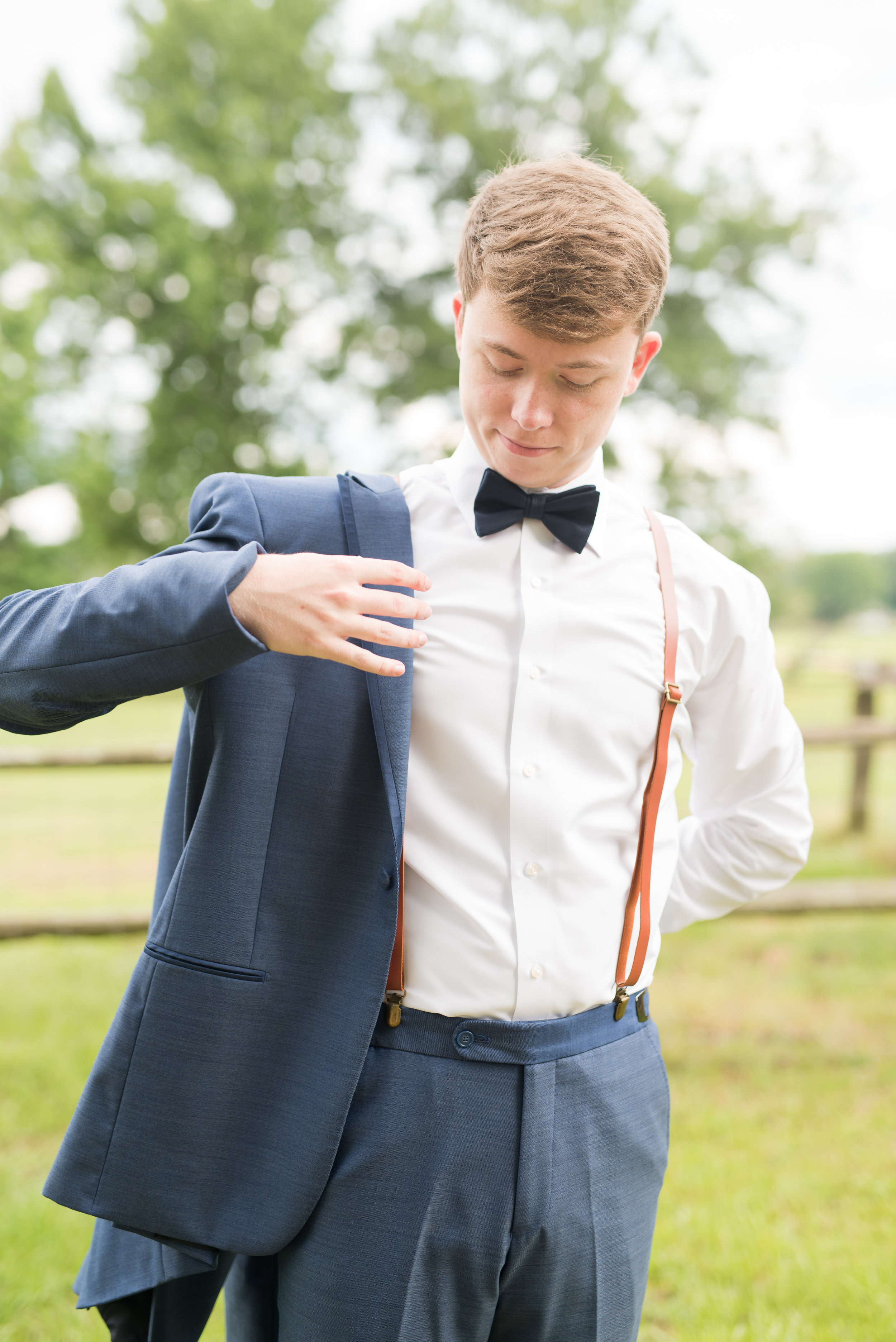 The Barn at Bridlewood wedding in Hattiesburg, Mississippi (MS) in June | Groom getting ready for wedding wearing suspenders and a bowtie