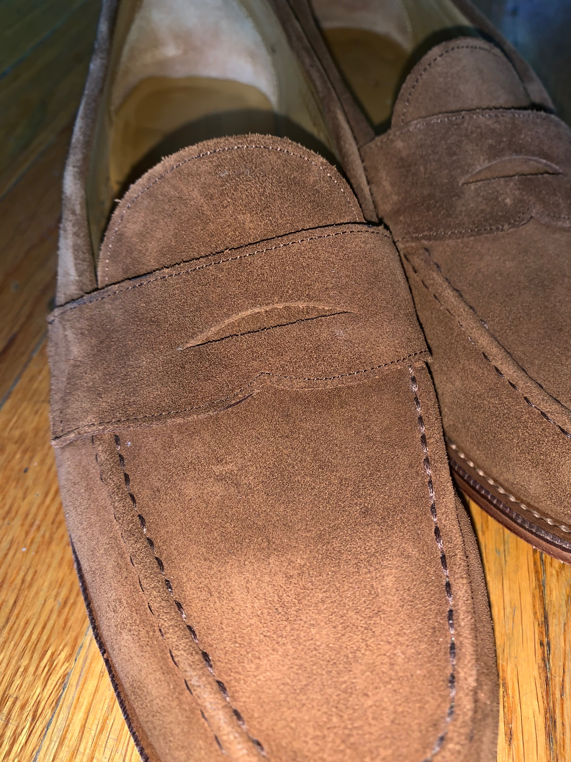 A close-up view of the snuff suede and circular penny loafer slot