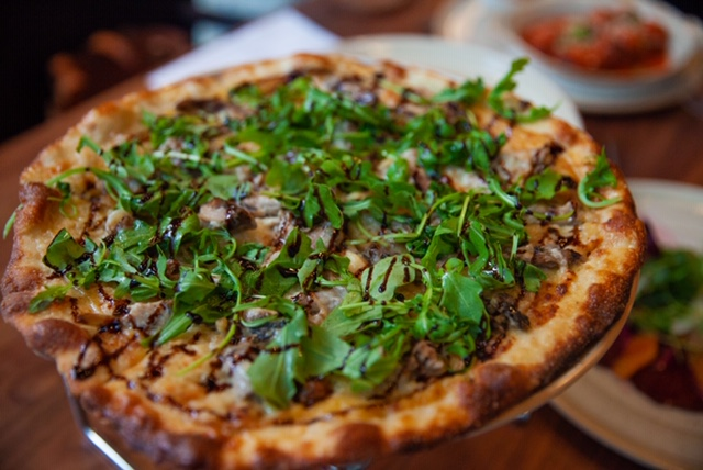 The delicious Duck Pizza topped with greens and a dash of garlic!