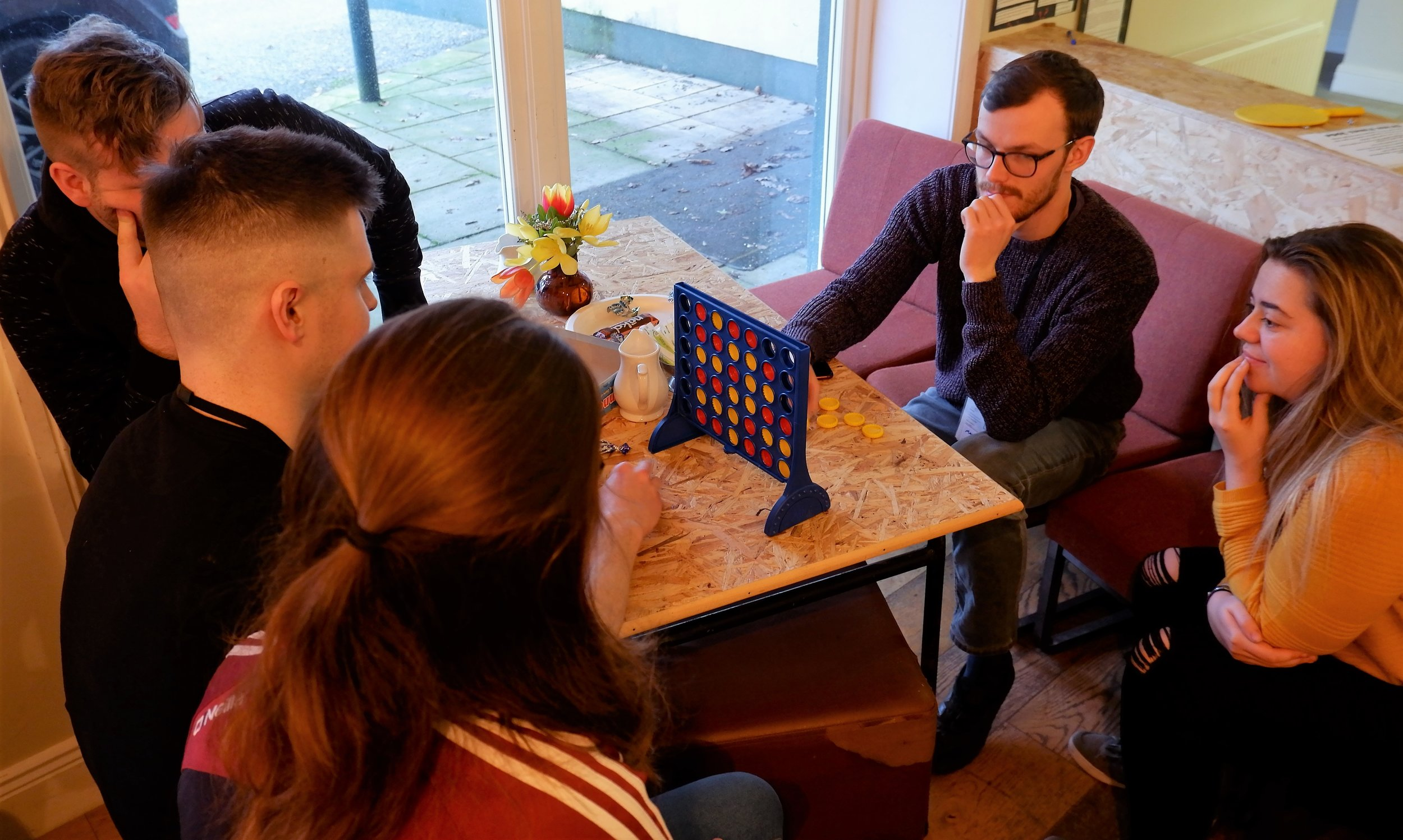 Some youth leaders playing a serious game of Connect 4 in the cafe!