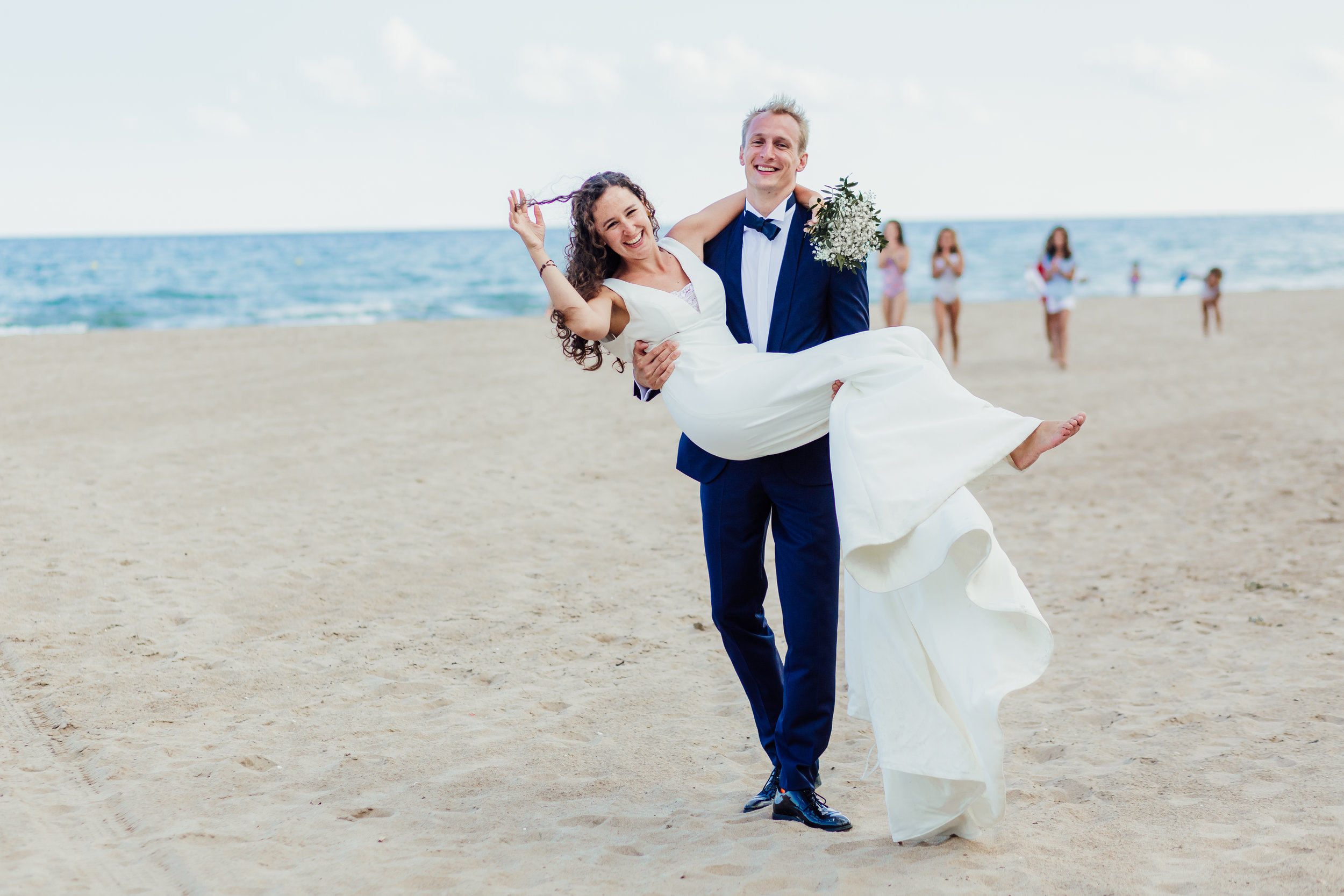 A bride and groom on the beach in Platja de Castelldefells on their wedding day at Almiral de la Font, Sant Pere de Ribes, Sitges, Barcelona by Jo Kemp Photography