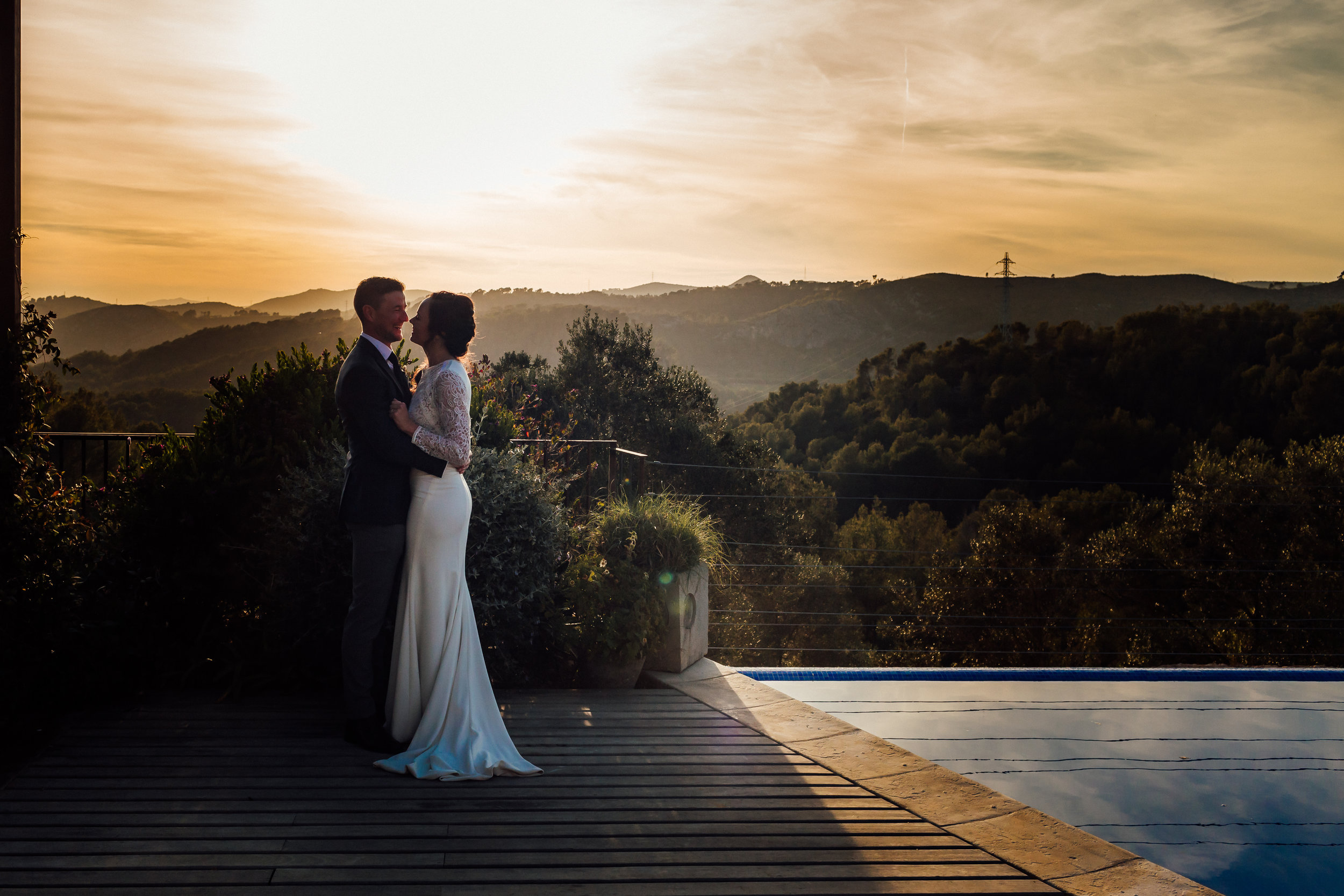 A bride and groom in front of a sunset by a swimming pool at Casa Felix, Sitges, Barcelona by Jo Kemp Photography
