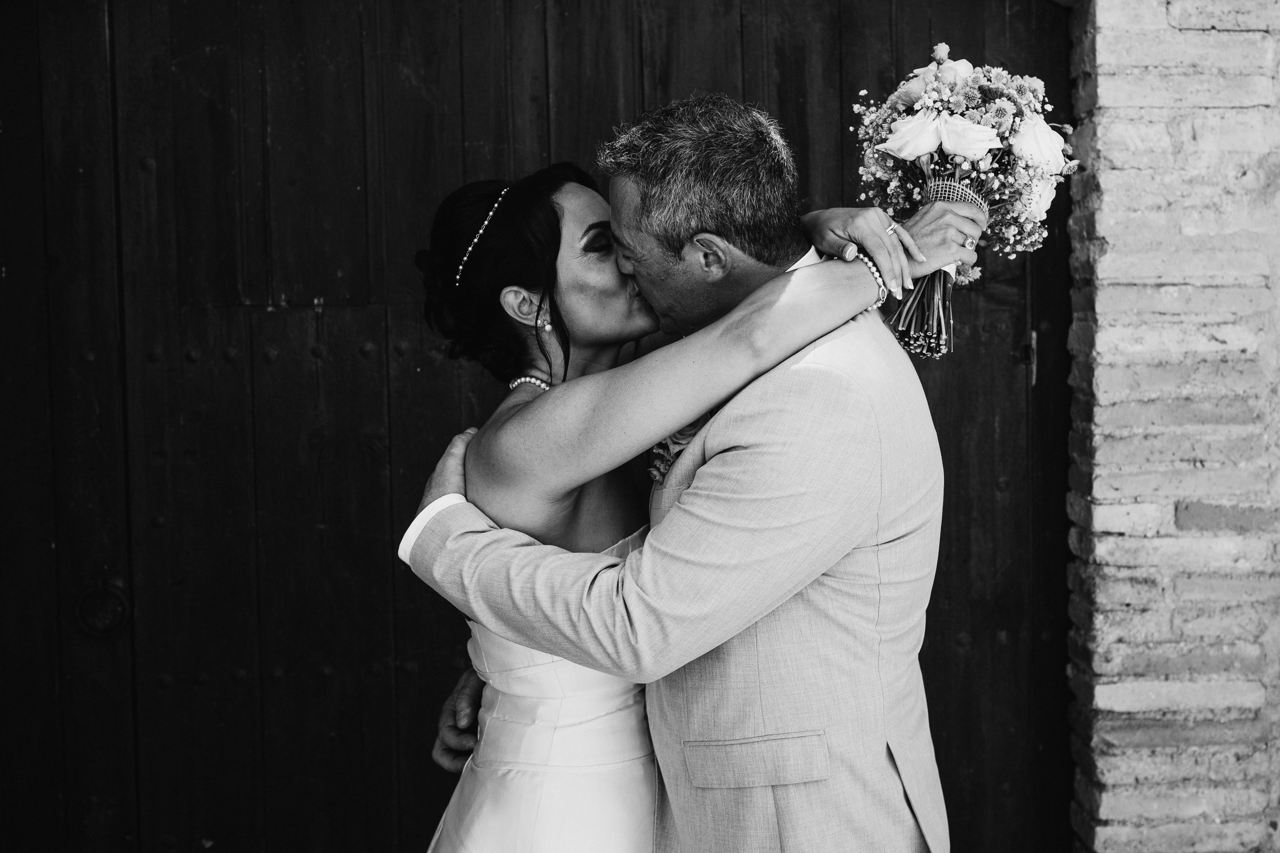 A bride and groom on their wedding day with a bouquet of flowers at Club House 27, Sitges, Vilanova, Barcelona by Jo Kemp Photography
