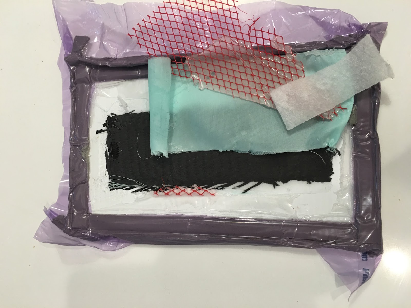 Contents of the vacuum bag: Stiff backing board (white); Carbon fiber (black); Peel ply (green) - removed after infusion; Flow media (red) - removed after; Absorbent batting (white) - removed after; Vacuum bag (purple); Tacky tape (grey) to seal the bag.