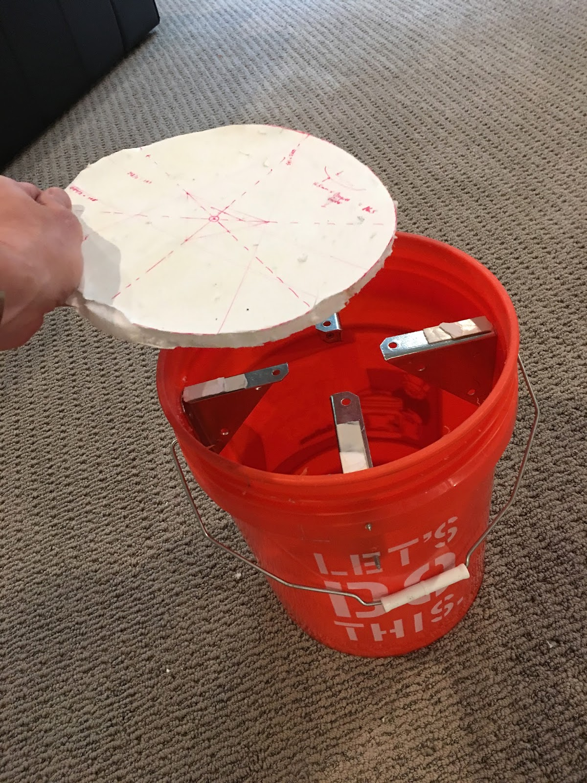 Inserting upper side of mold into bucket. Metal brackets are covered with foam tape. This whole assembly will be turned upside down during molding. Foamcore board is a little chewed up because I took this pic after de-molding 2 pads.