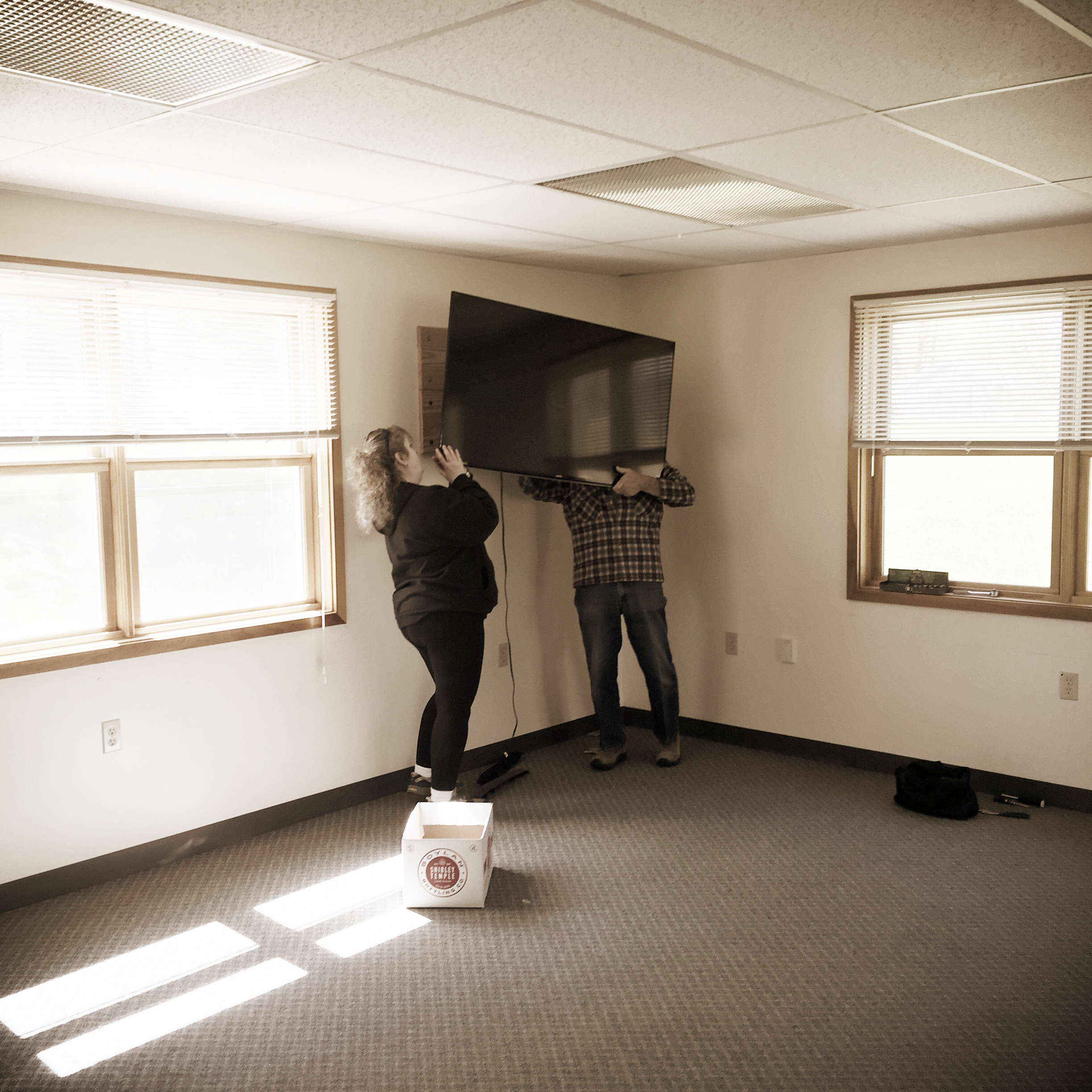 Dee Dee and Geoff (board member) taking down our mounted television