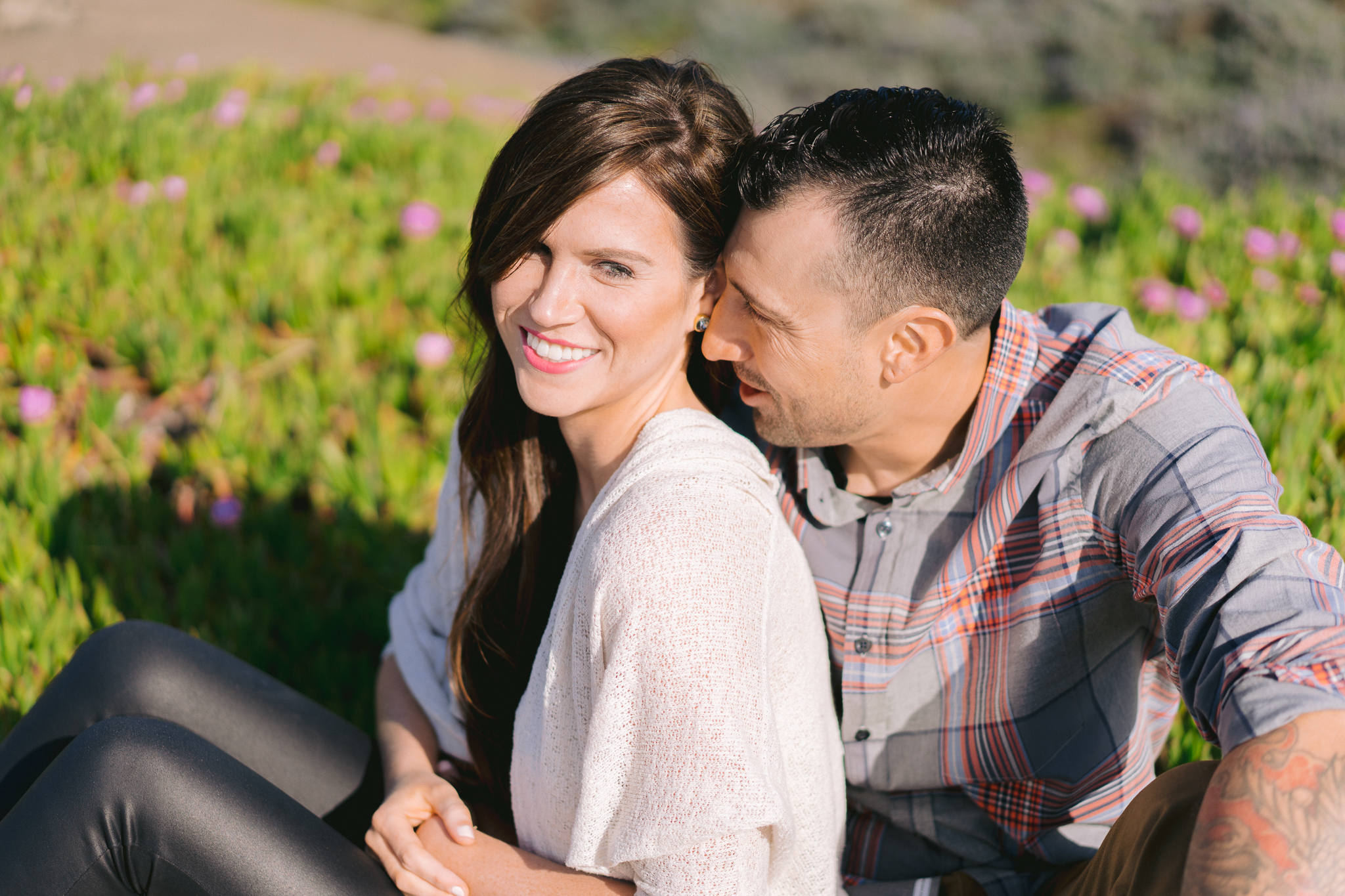 Romantic engagement photo of couple sitting in flower field in San Francisco Park near Baker Beach and Battery Chamberlin.