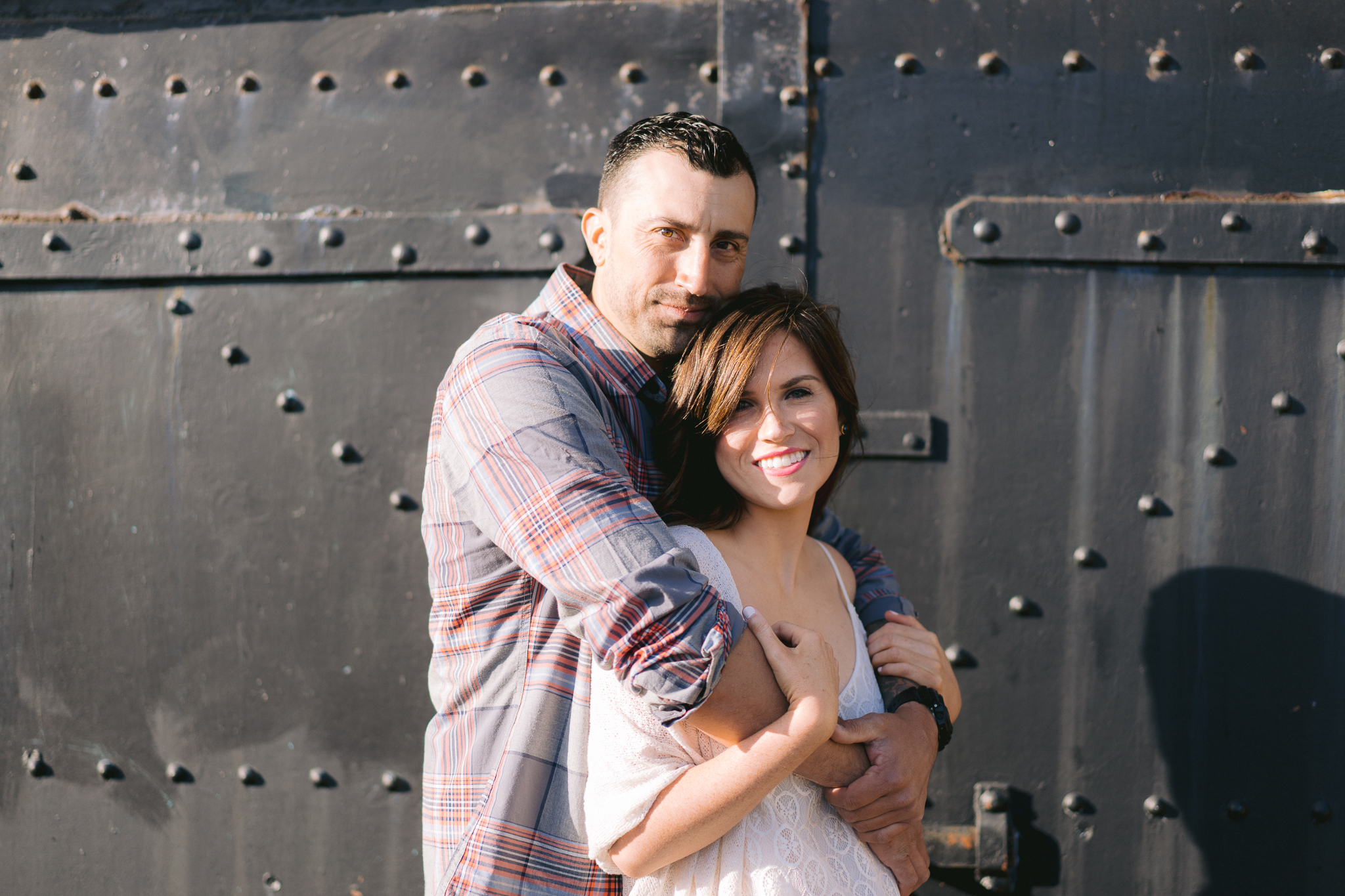 Romantic shot of couple with woman smiling during Engagement shoot in front of Battery Chamberlin.