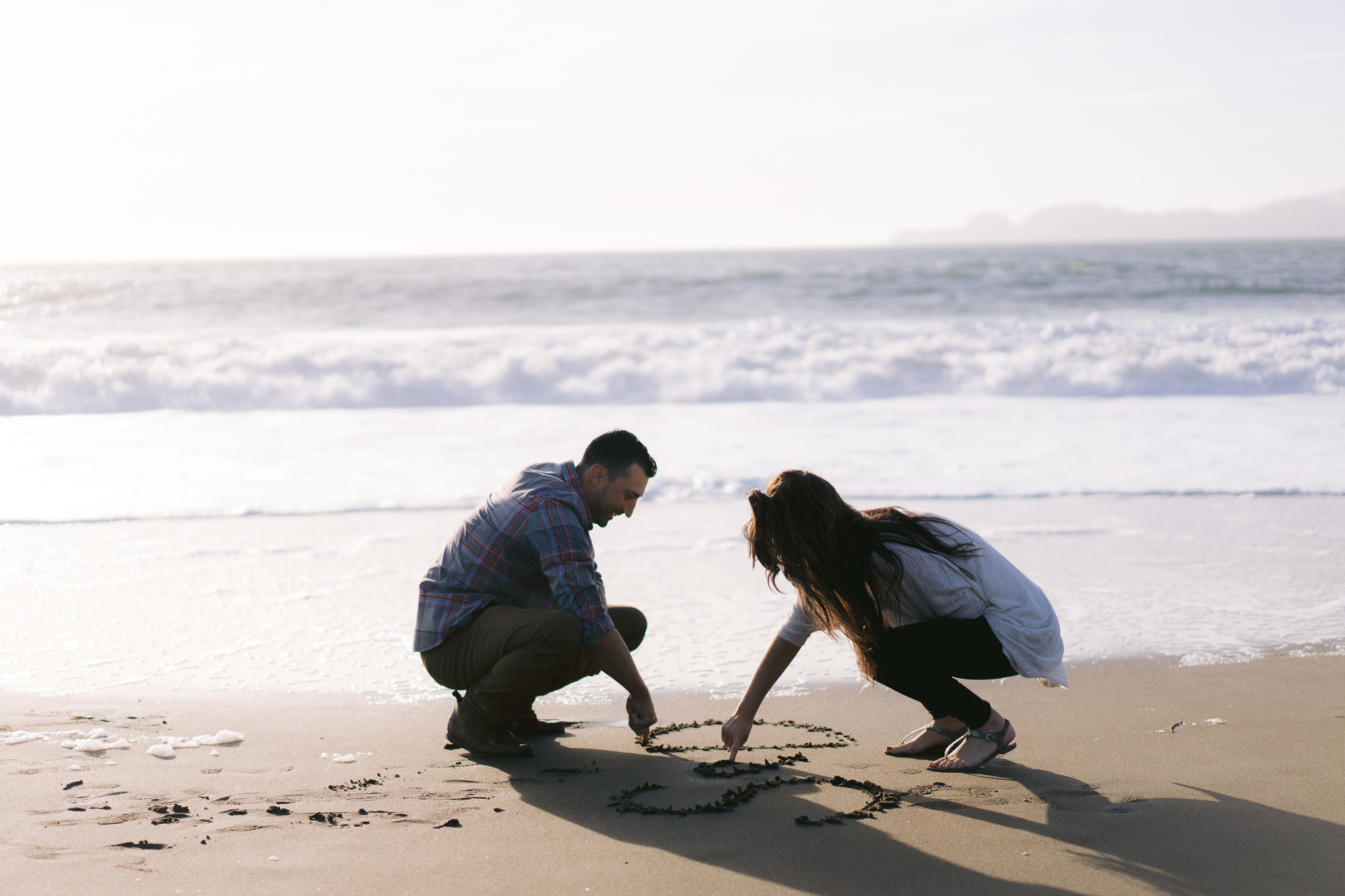 Couple drawing initials in the sand at Baker Beach engagement session.
