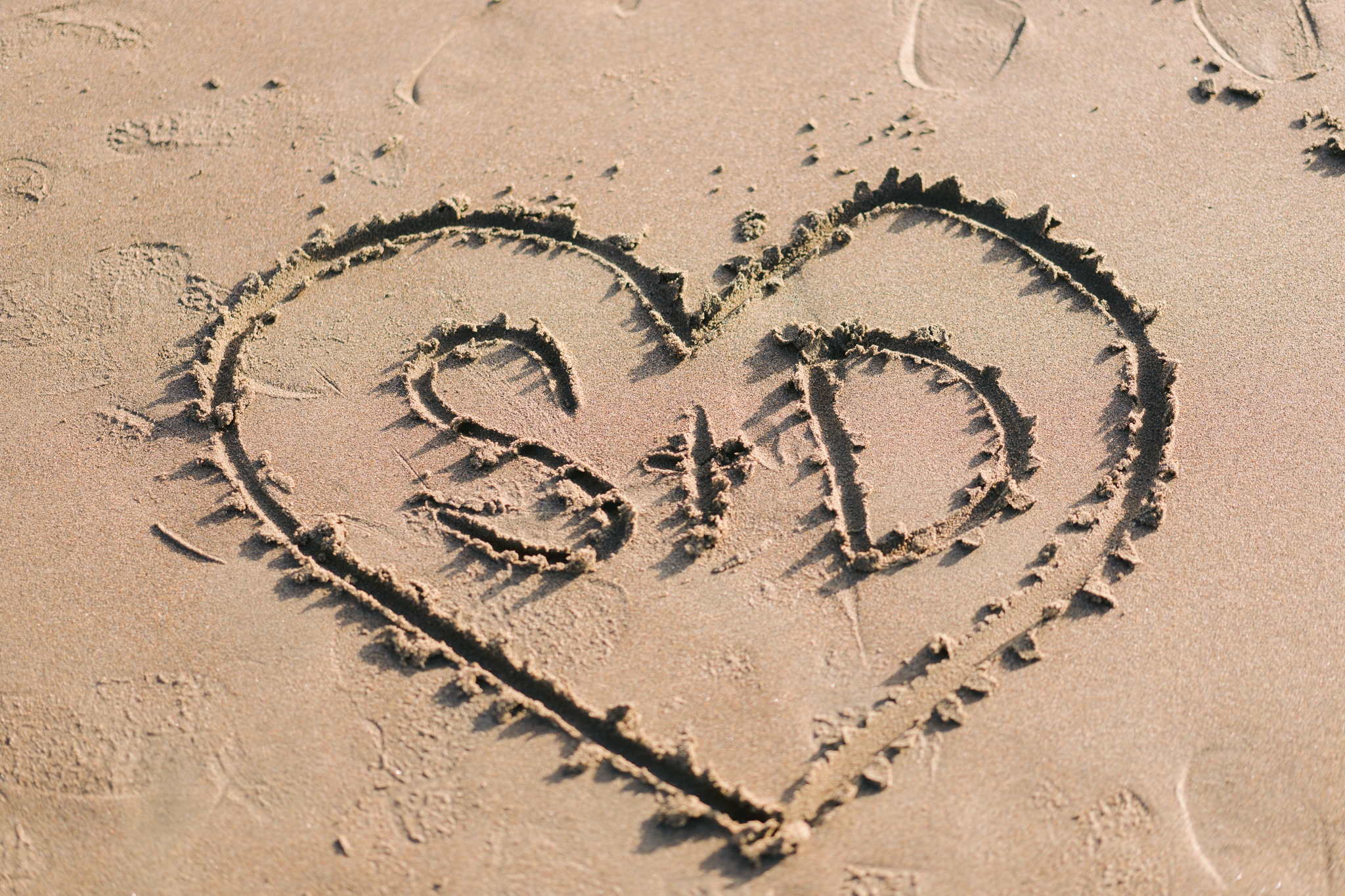 Beach engagement picture with initials S + D drawn in the sand with a heart drawn around them.