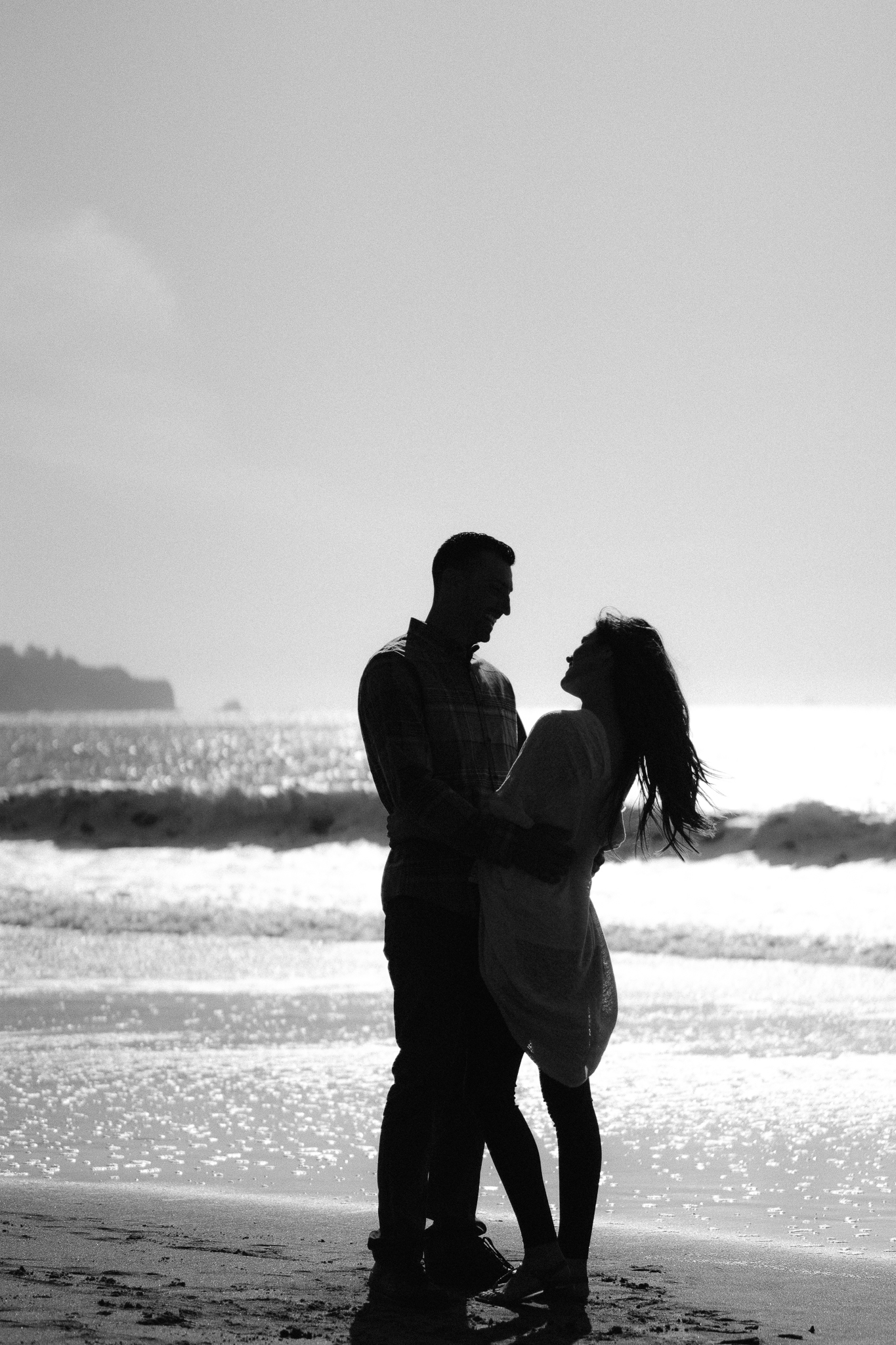 Engaged couple writing their initials in the sand at Baker Beach in San Francisco during their romantic sunset photo shoot celebrating their engagement.