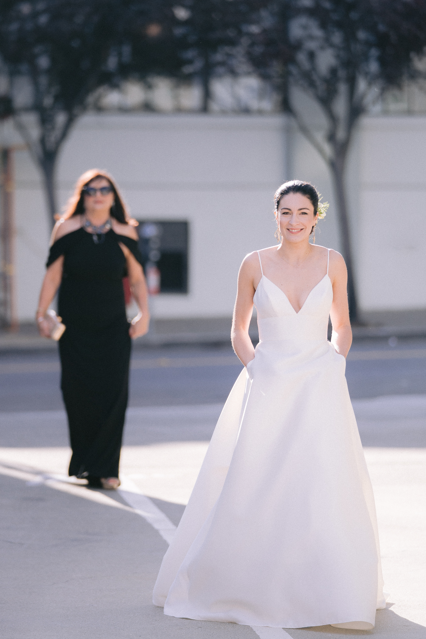 bride walking in san francisco streets with mother behind her