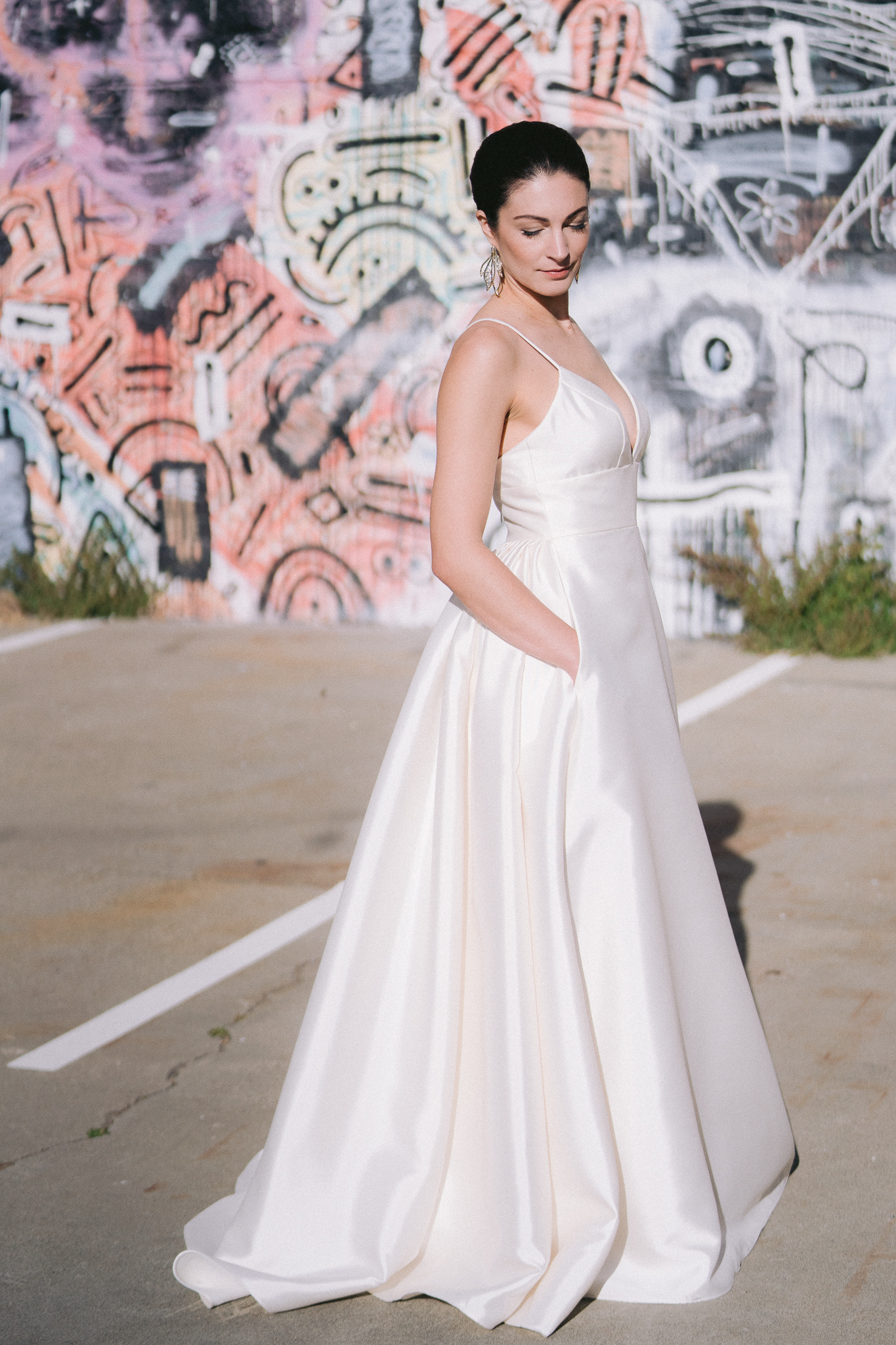 fine art portrait of bride in wedding dress with hands in pockets in front of graffiti wall in san francisco