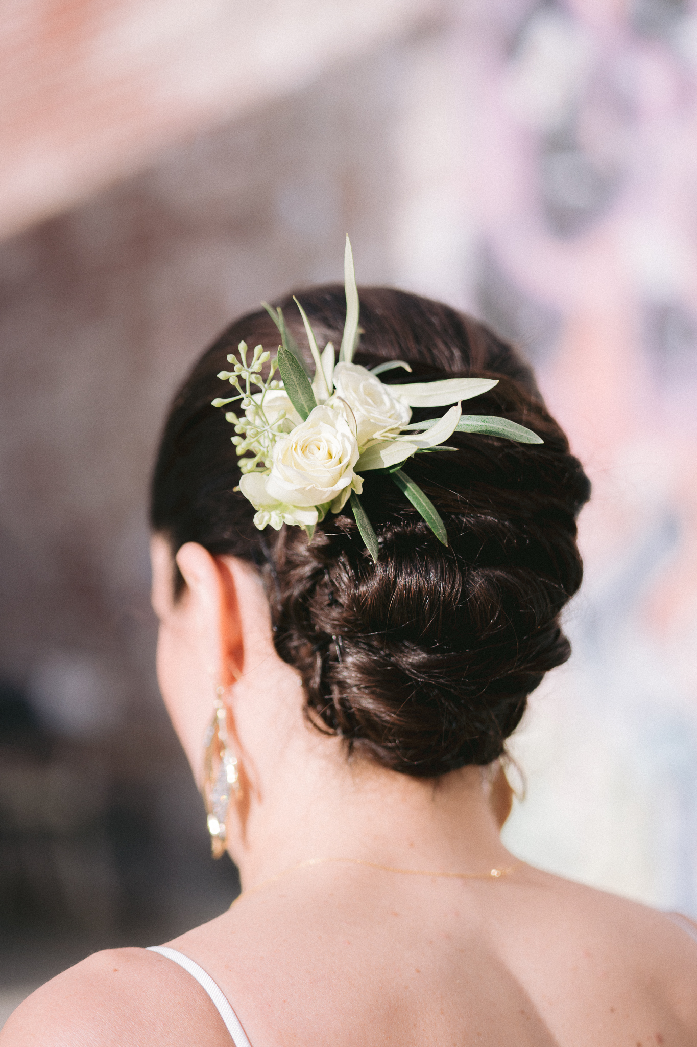 close up of bridal hair style with a flower in urban san francisco street backdrop