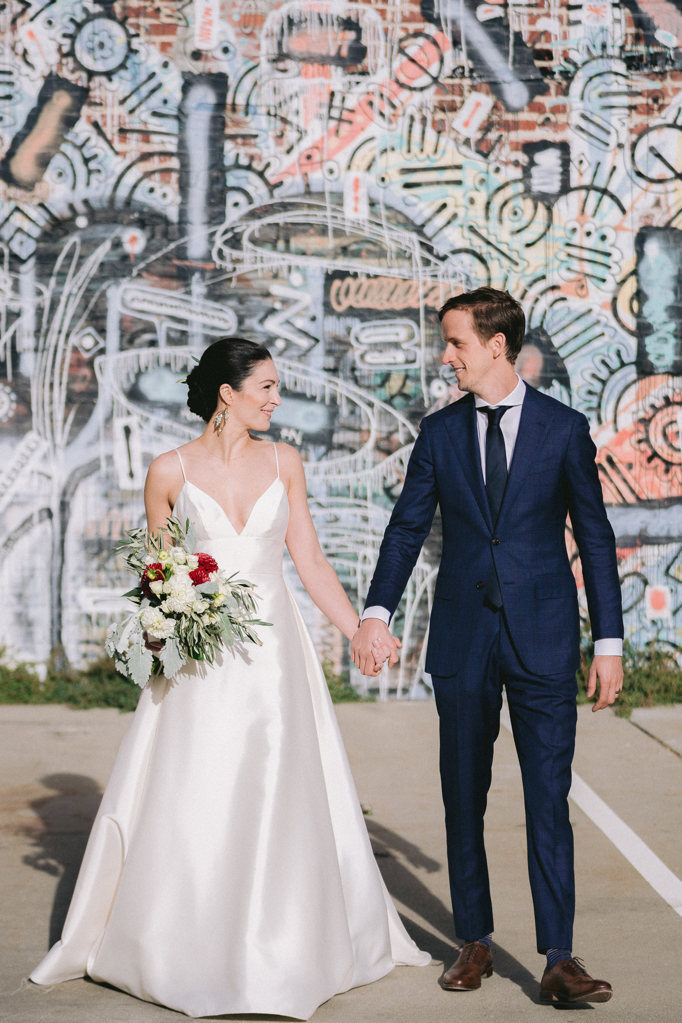 wedding photo of bride and groom holding hands in front of a graffiti wall in San Francisco, CA.