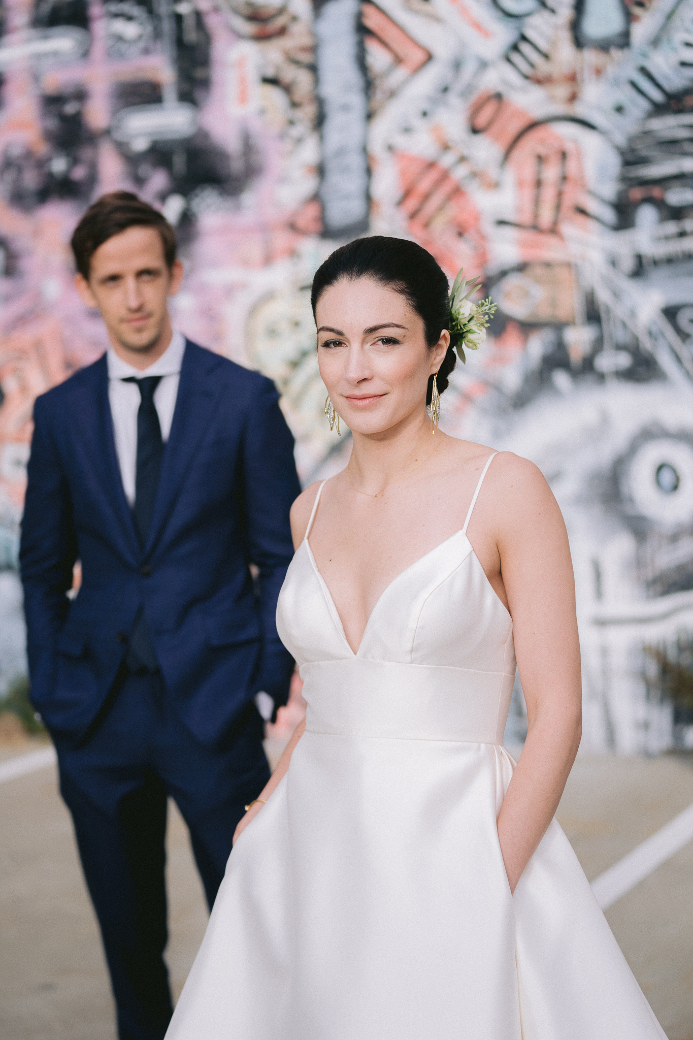 fine art portrait wedding photo in front of graffiti wall in san francisco - bride is in focus and groom is blurred out in the background.