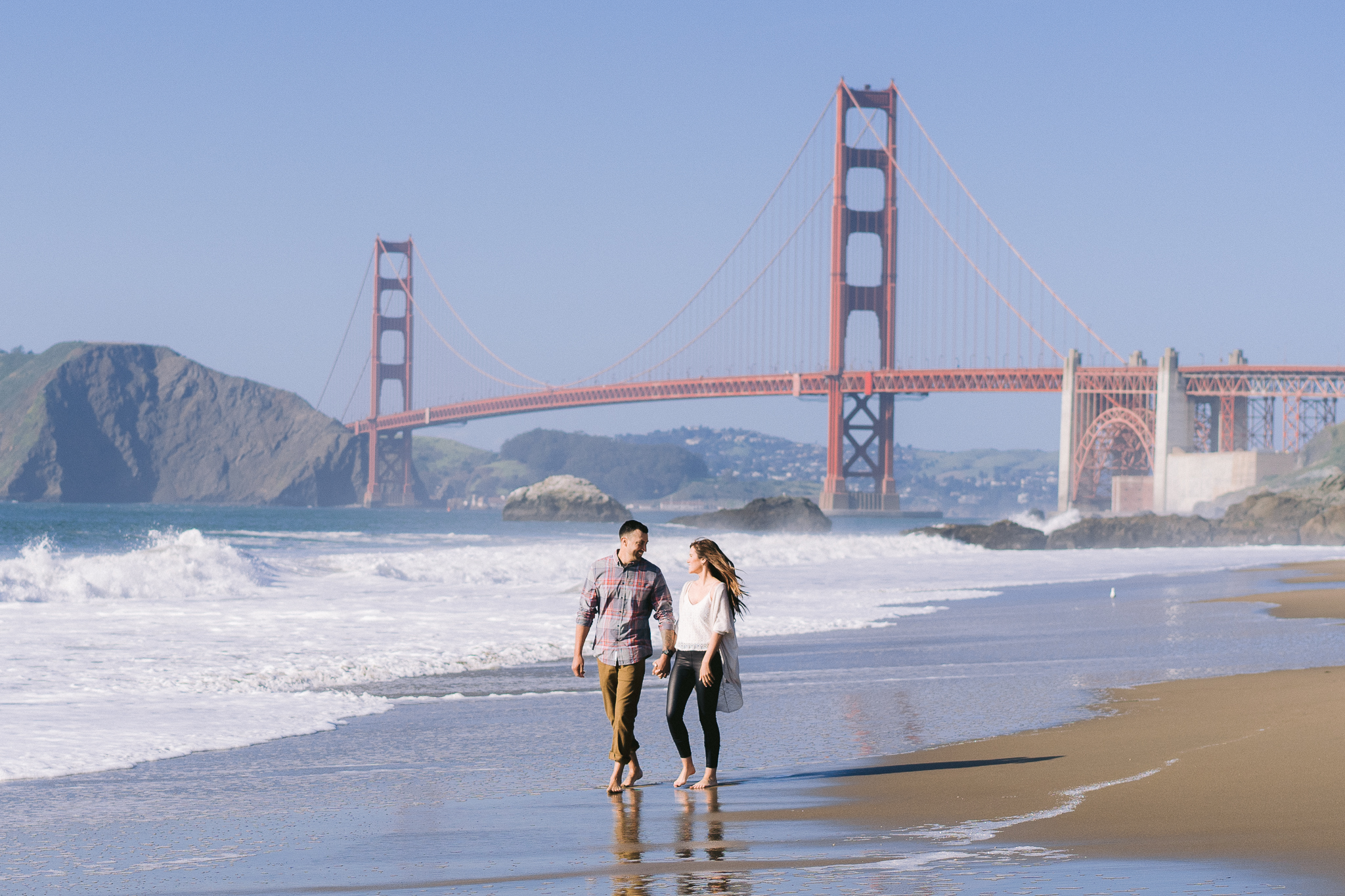 Engaged Couple Stephanie and Danny strolling along Baker Beach hand in hand in front of the Golden Gate Bridge during an Engagement Photo Shoot in San Francisco, CA.