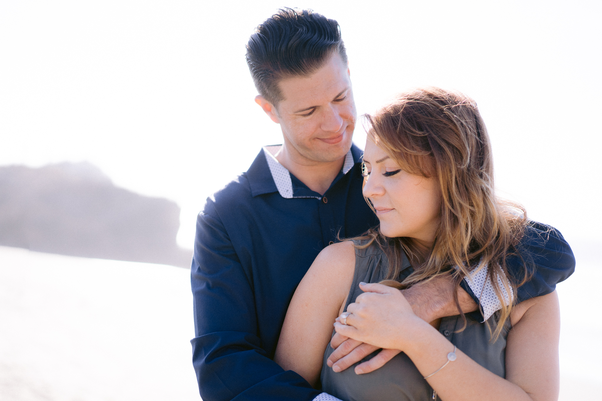 Close up engagement photo of an engaged couple embracing in front of the Pacific Ocean at the Sutro Baths in San Francisco.