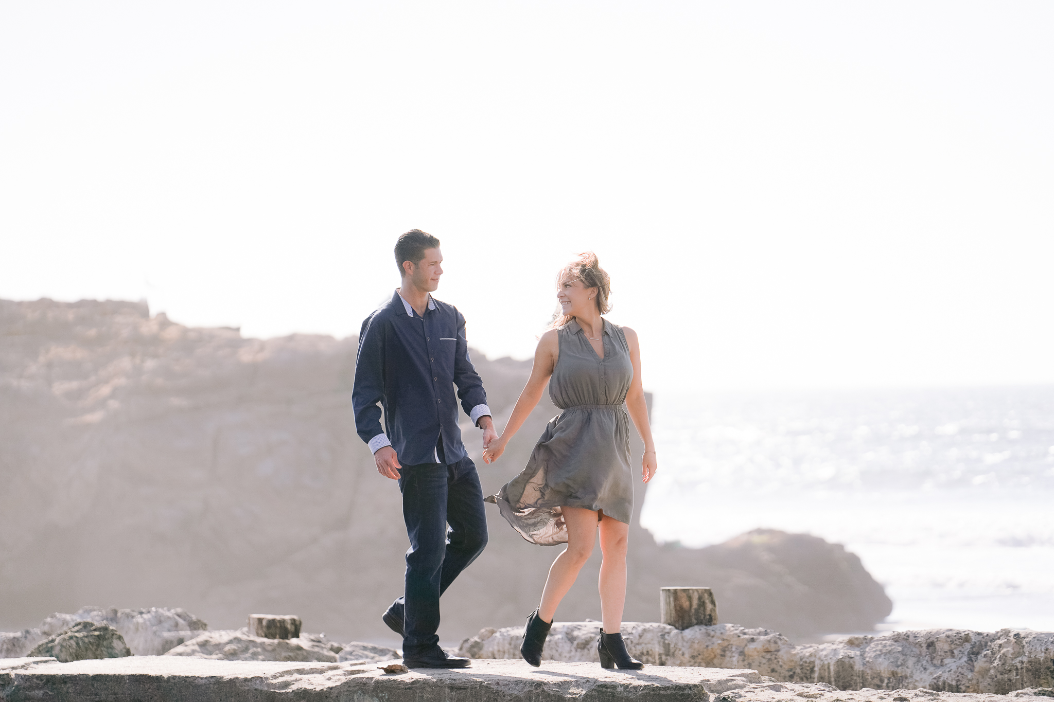 San Francisco engagement photo of couple holding hands and walking along the ruins of the Sutro Baths structure.